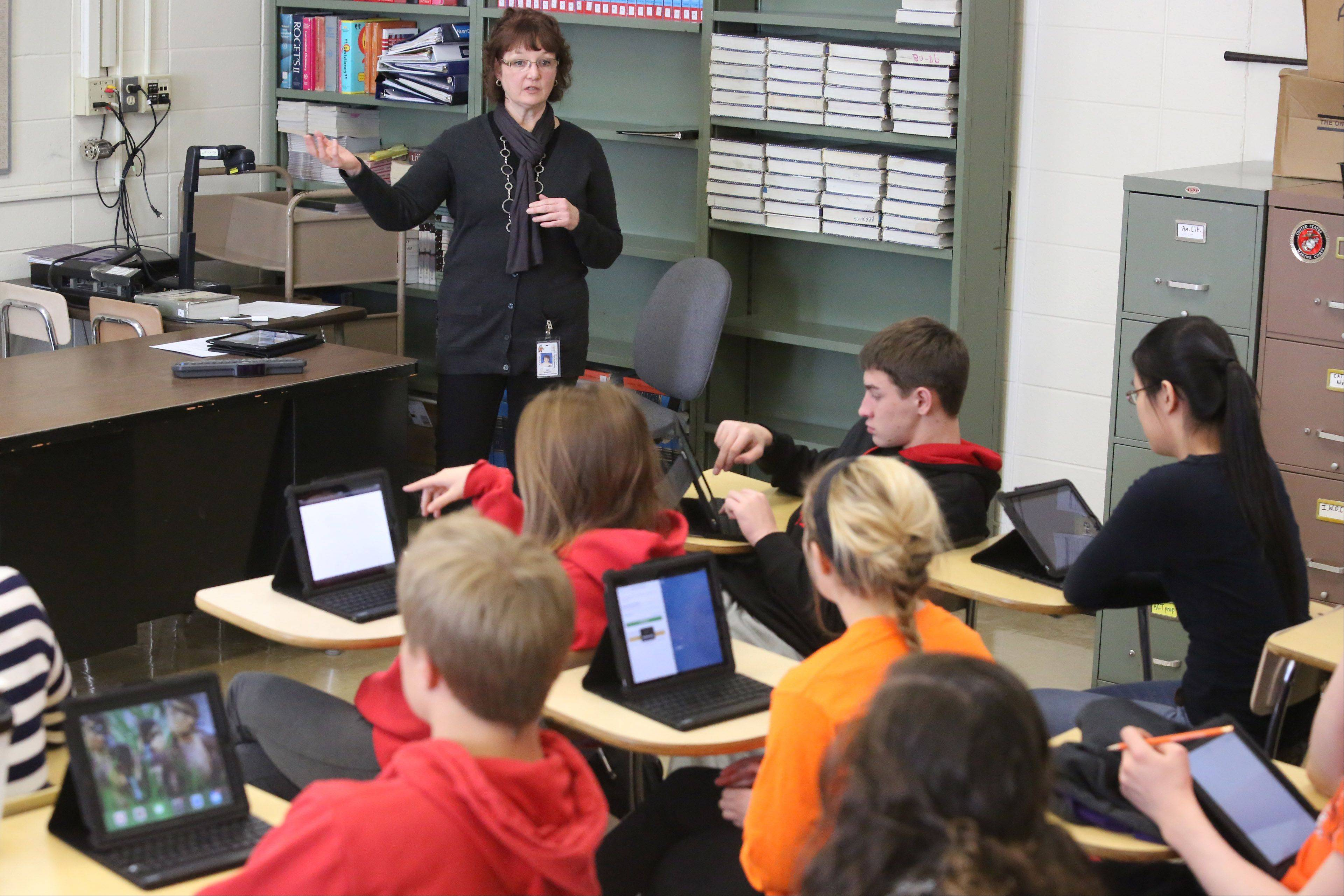 Alexander teaches juniors in Kent Manthey's Advanced Placement English, Language, and Composition class how to download and view or listen to public domain books on iPads issued to them.