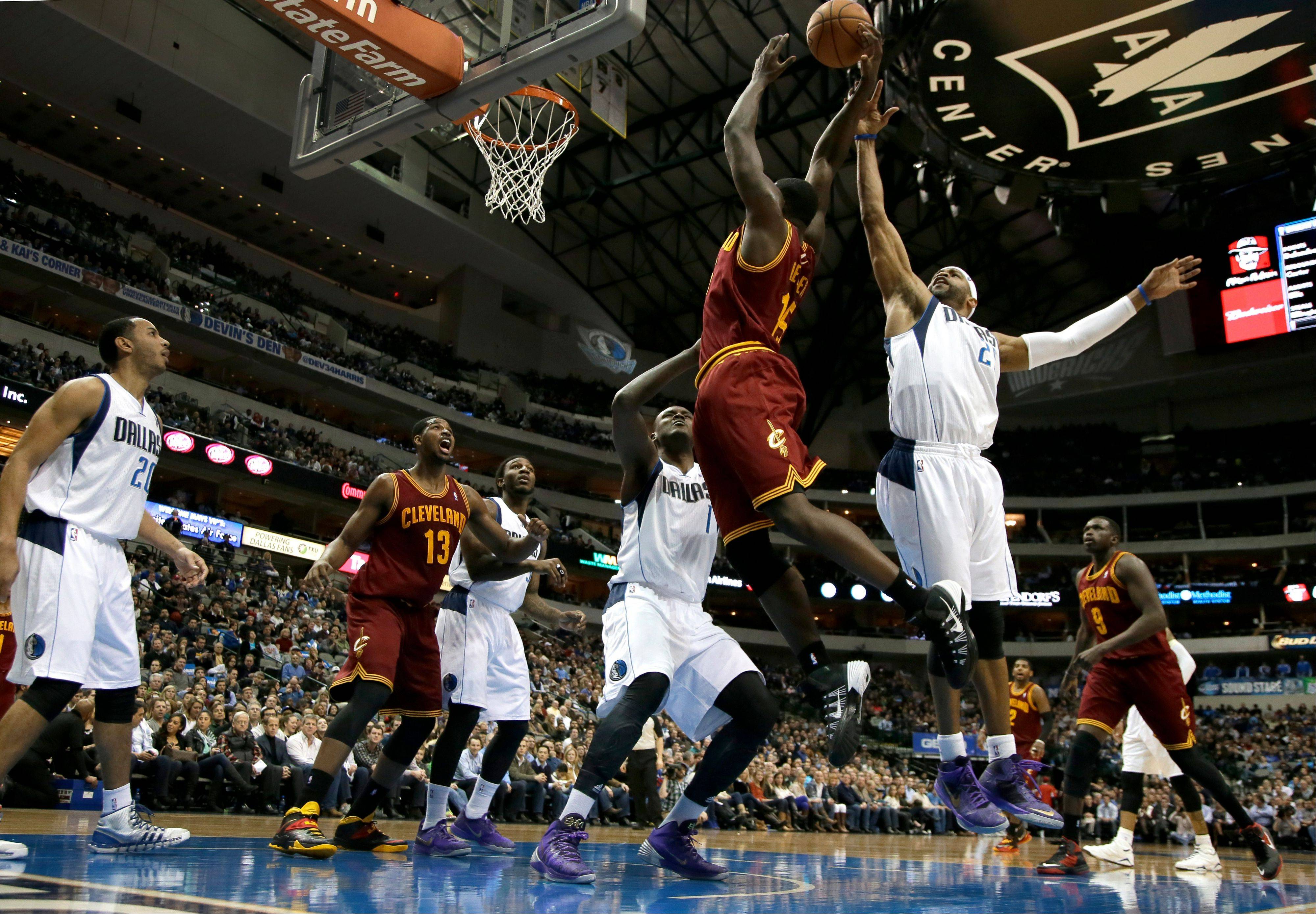 Cleveland Cavaliers forward Anthony Bennett (15) has the ball slapped away on a dunk attempt by Dallas Mavericks' Vince Carter (25) as Devin Harris (20), Tristan Thompson (13), Jae Crowder, center rear, Samuel Dalembert (1) of Haiti and Luol Deng (9) of Sudan watch in the first half of an NBA basketball game, Monday, Feb. 3, 2014, in Dallas.