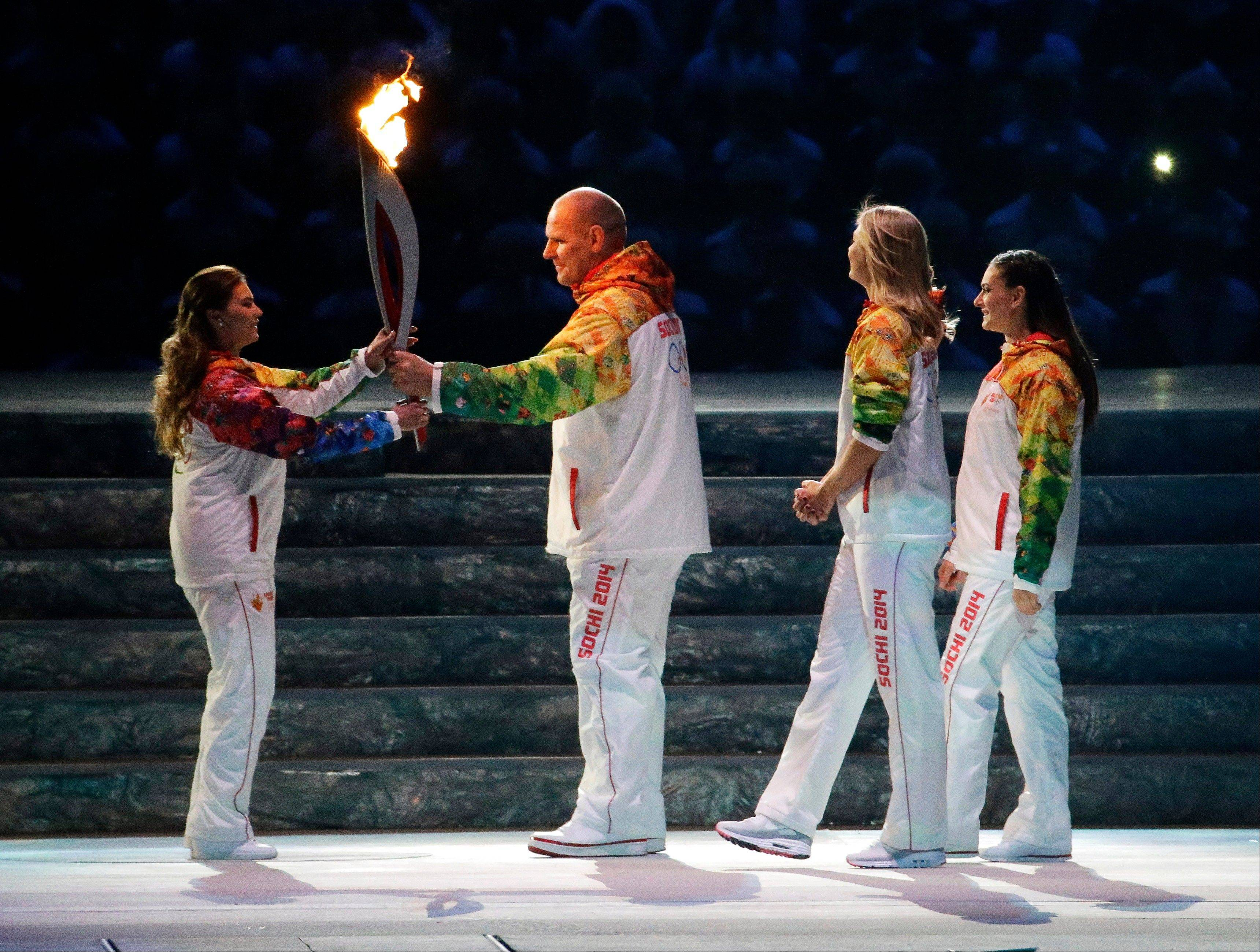 Russian wrestler Alexander Karelin, second from left, hands the torch to Russian gymnast Alina Kabaeva, left, as Russian tennis player Maria Sharapova, second from right, and Russian pole vaulter Yelena Isinbayeva look on during the opening ceremony.
