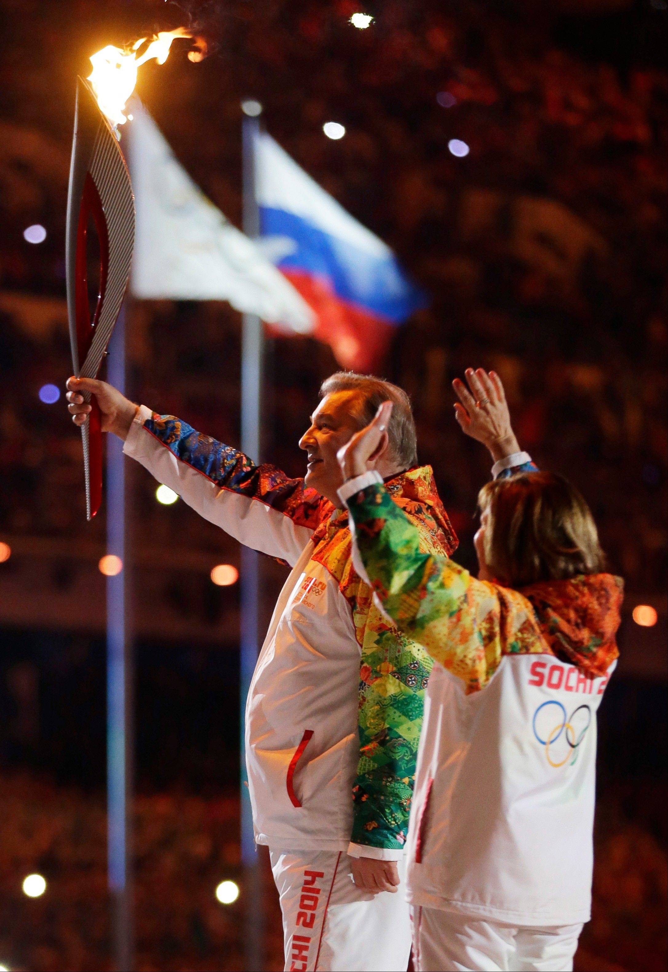 Vladsilav Tretyak holds the torch during the opening ceremony.