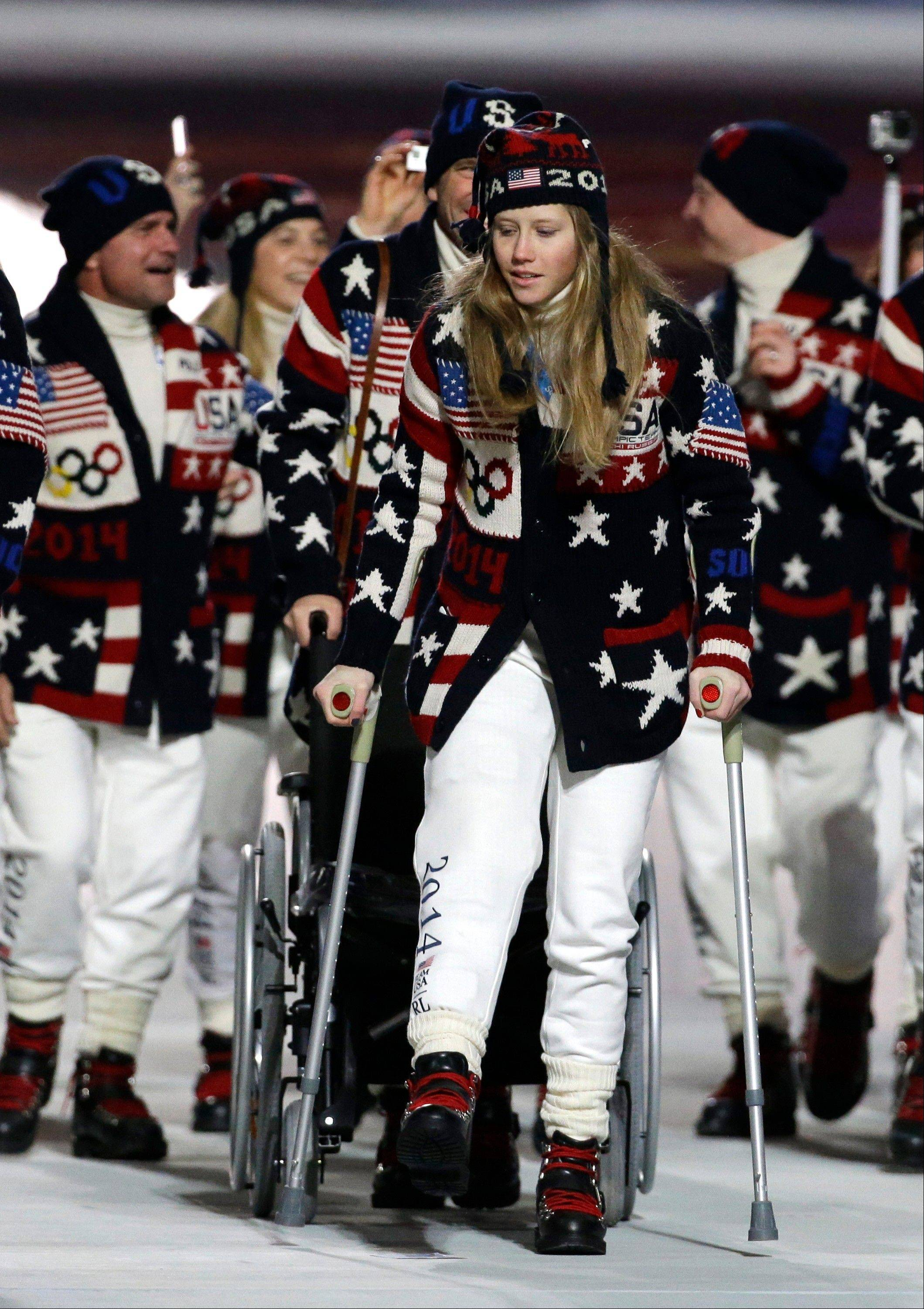 Freeskier Heidi Kloser of the United States walks on crutches after she injured her right leg during a training run before moguls qualifying as she arrives for the opening ceremony.