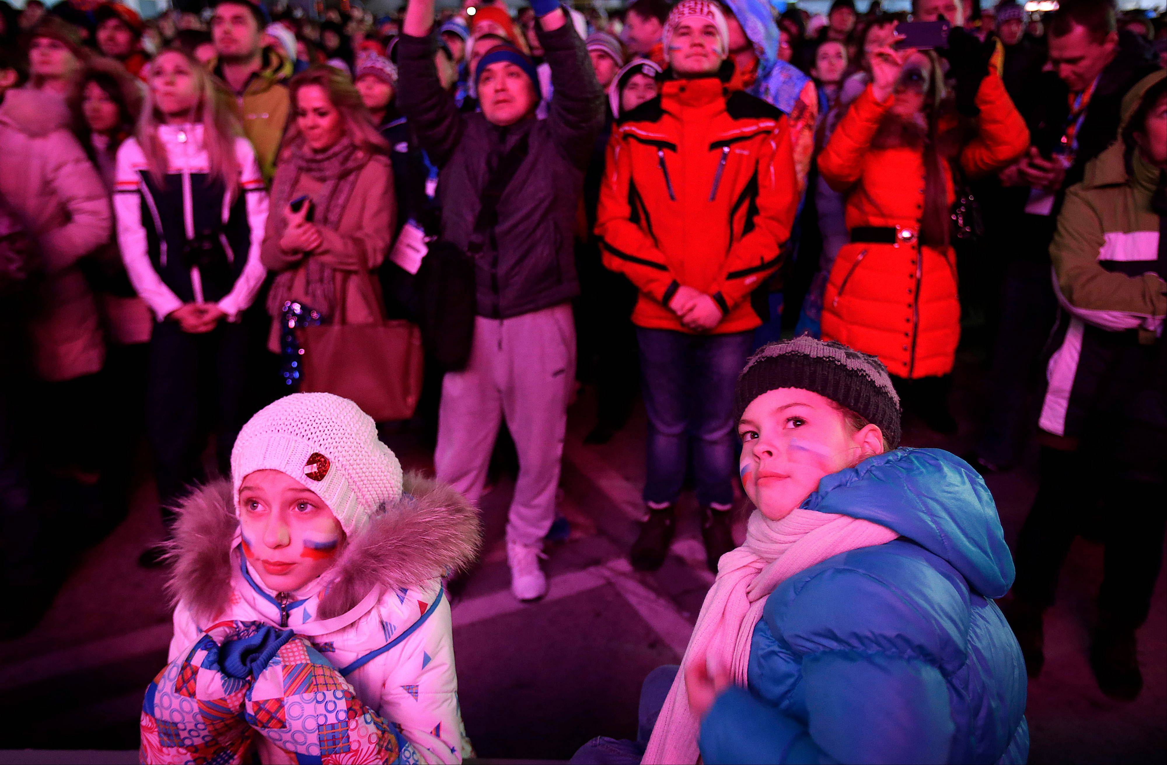 Young Russian girls watch intensely as the live telecast of the 2014 Winter Olympics opening ceremony is broadcast on giant screens, Friday, Feb. 7, 2014, in downtown Sochi, Russia.