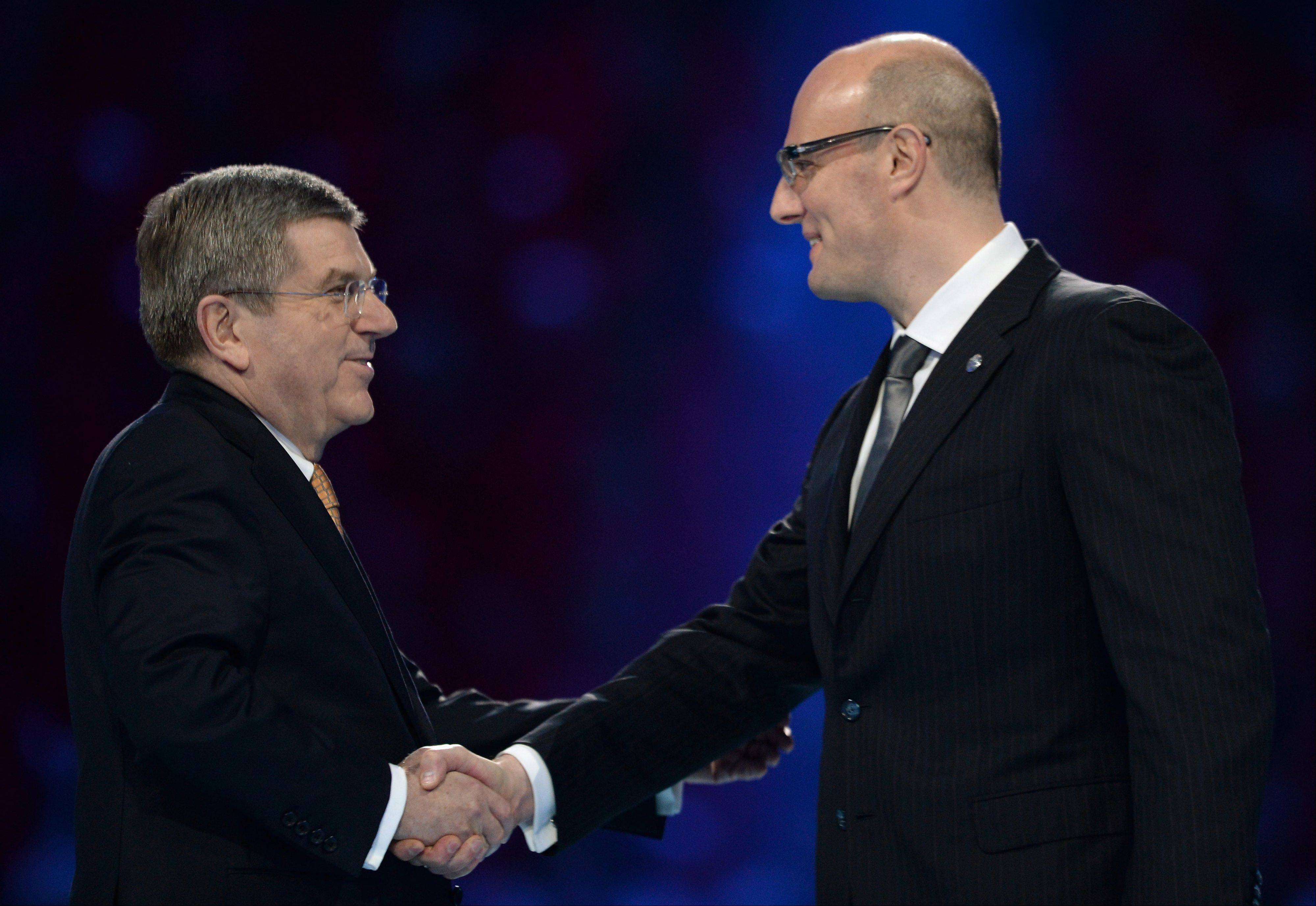International Olympic Committee President Thomas Bach, left, shakes hands with President and CEO of the Sochi 2014 organizing committee Dmitry Chernyshenko during the opening ceremony.