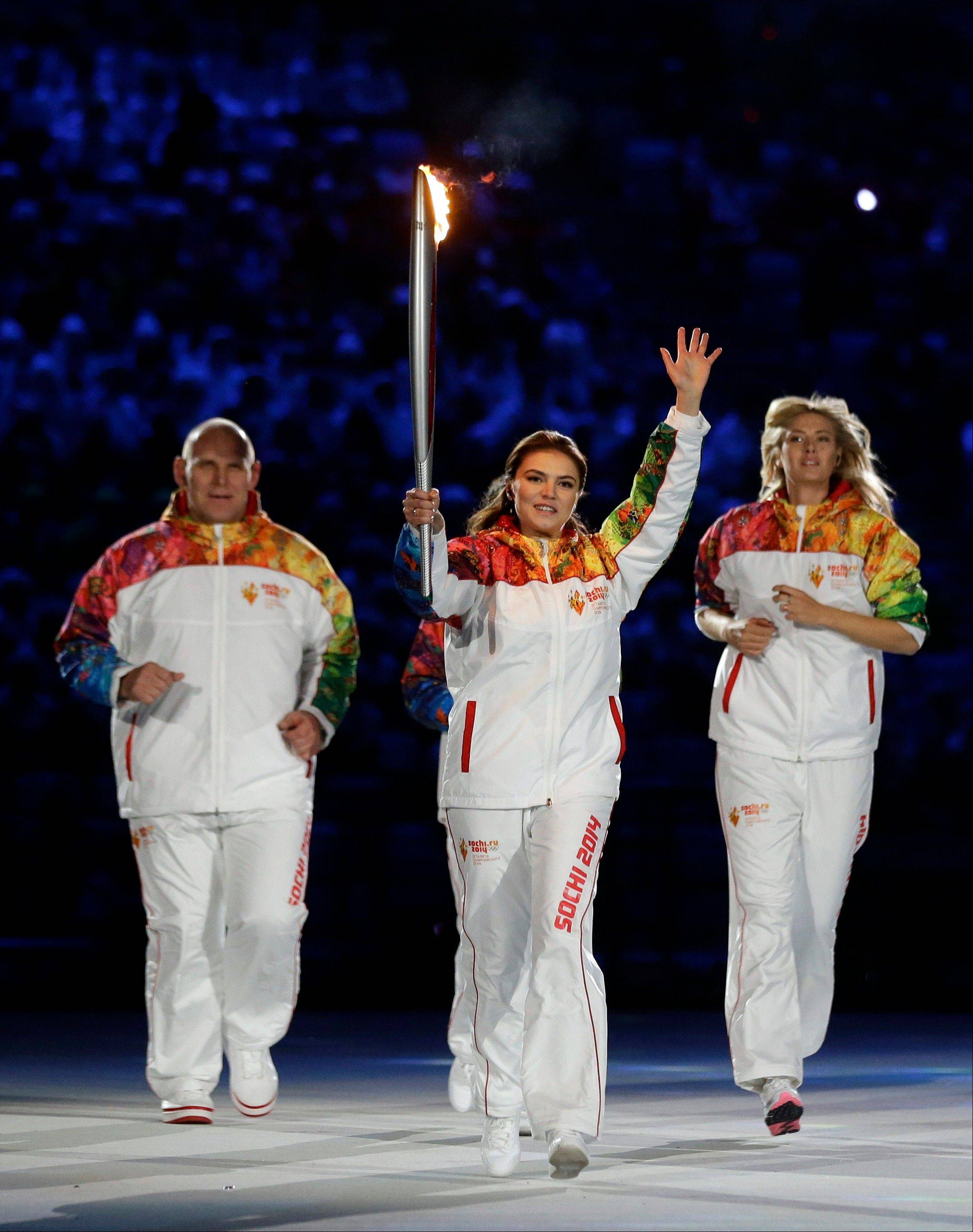 Alina Kabaeva holds the torch flanked by Maria Sharapova, right, and Alexandr Karelin during the opening ceremony .