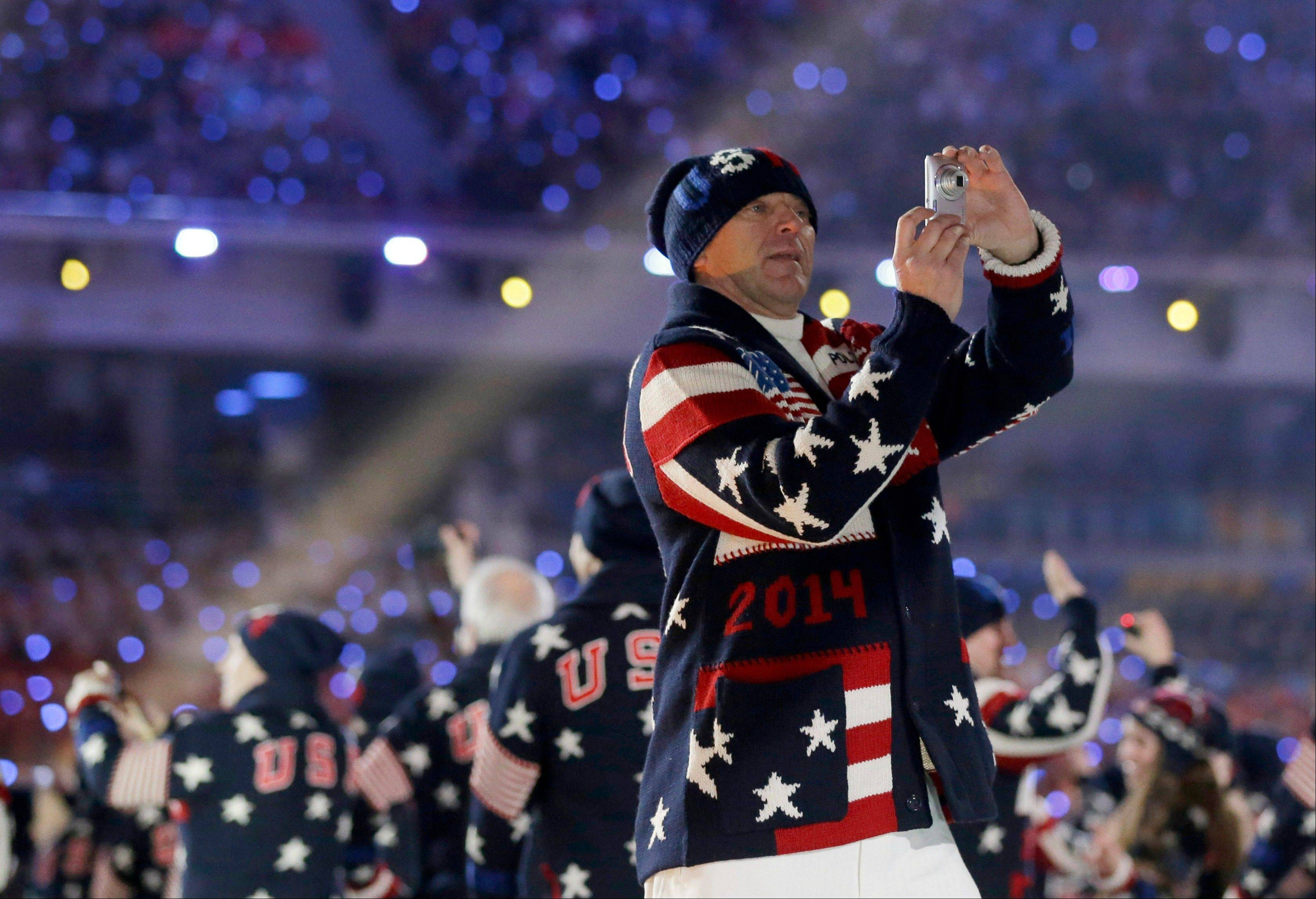 A member of the United States team takes pictures as he enters the stadium during the opening ceremony.