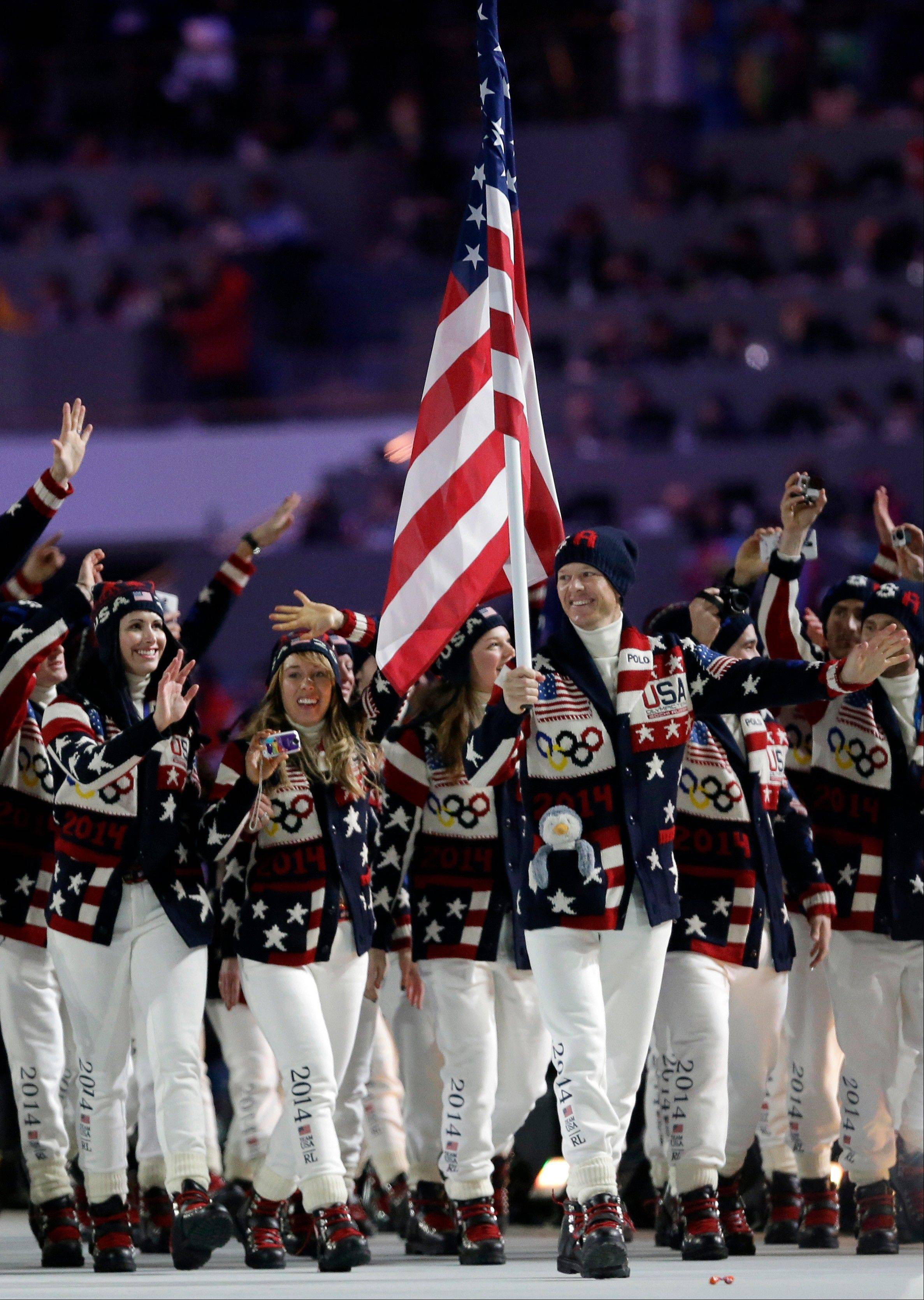 Todd Lodwick of the United States carries the national flag as he leads his team into the stadium during the opening ceremony .