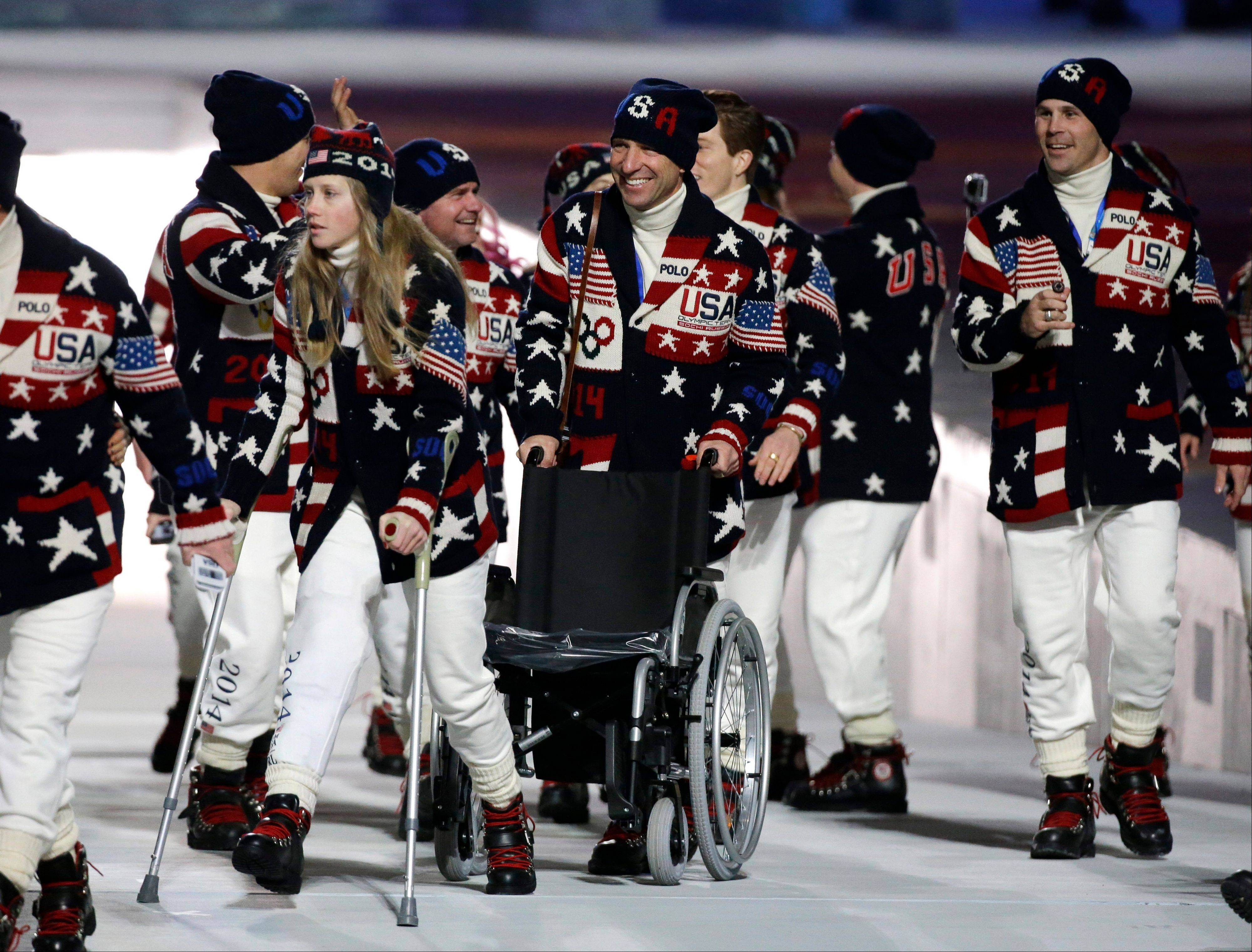 Freeskier Heidi Kloser of the United States, left, walks on crutches after she injured her right leg during a training run before moguls qualifying as she arrives for the opening ceremony.
