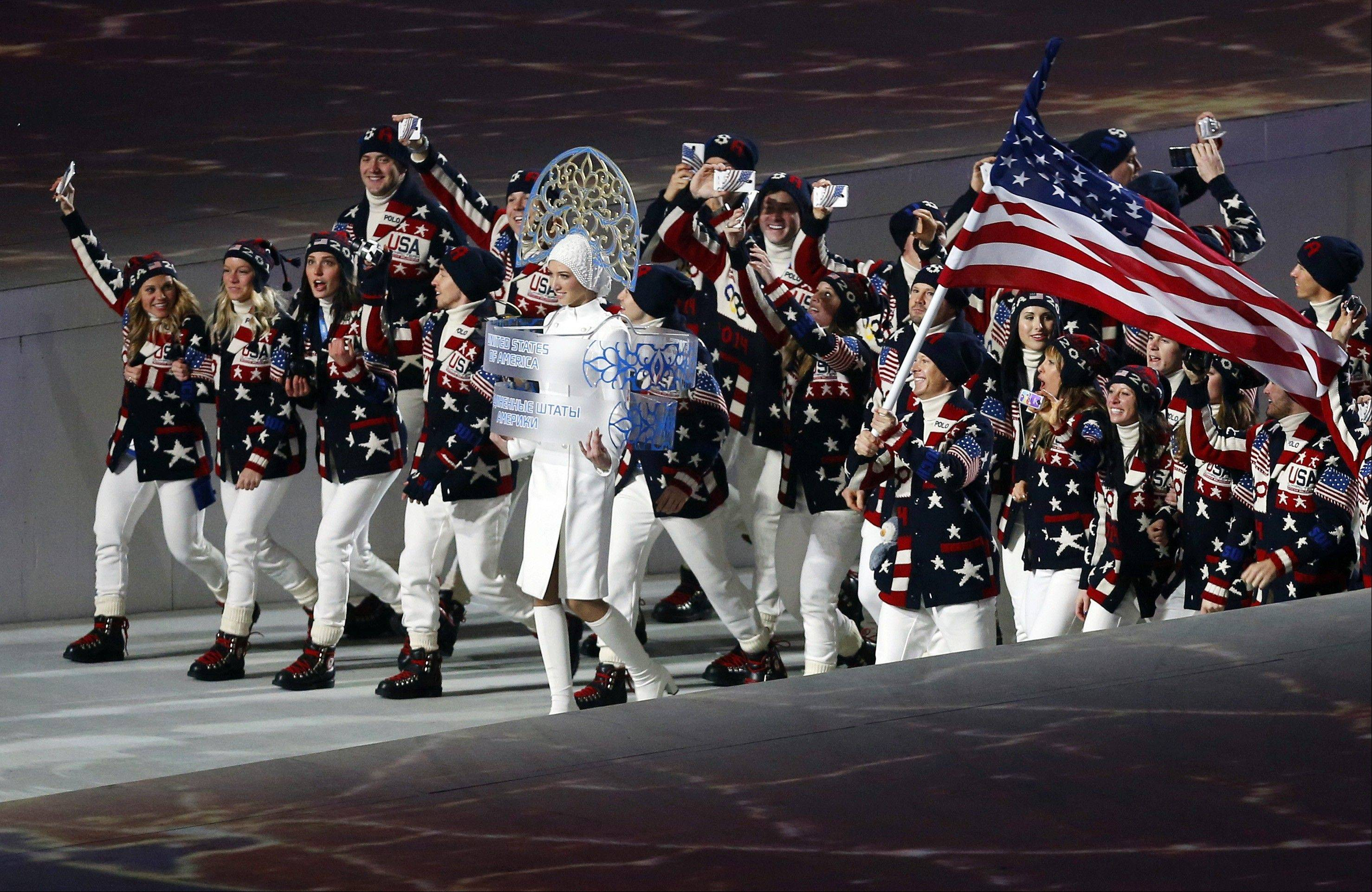 Todd Lodwick of the United States carries his country flag as the team arrives during the opening ceremony.