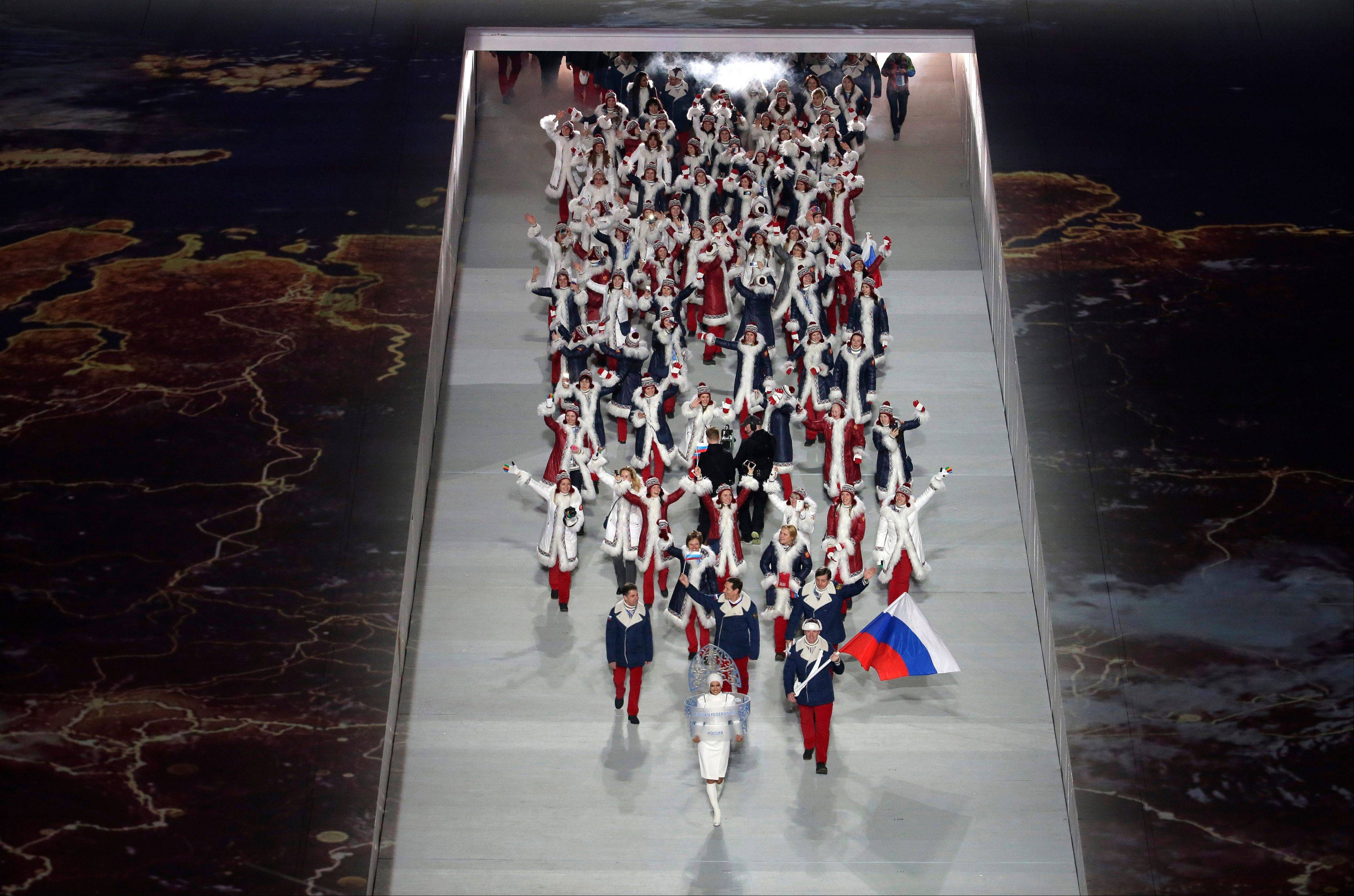 Alexander Zubkov of Russia holds her national flag and enters the arena with teammates during the opening ceremony.
