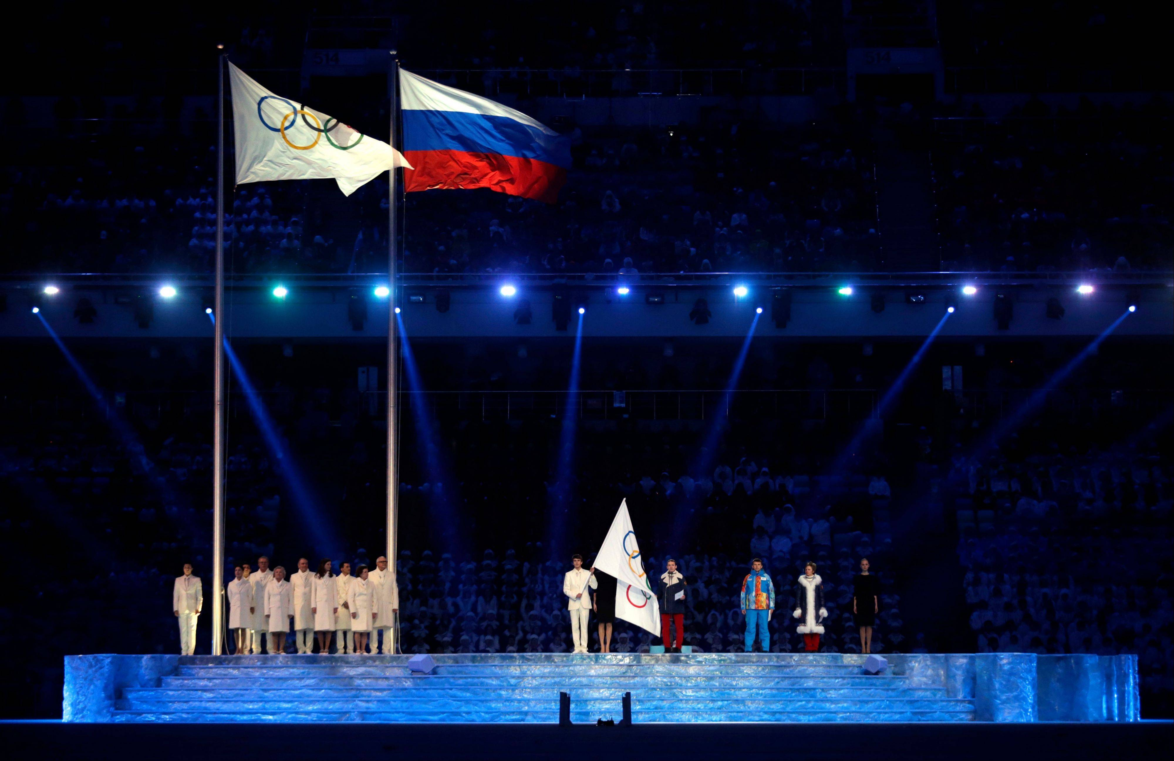 The Olympic and the Russian flags wave during the opening ceremony.