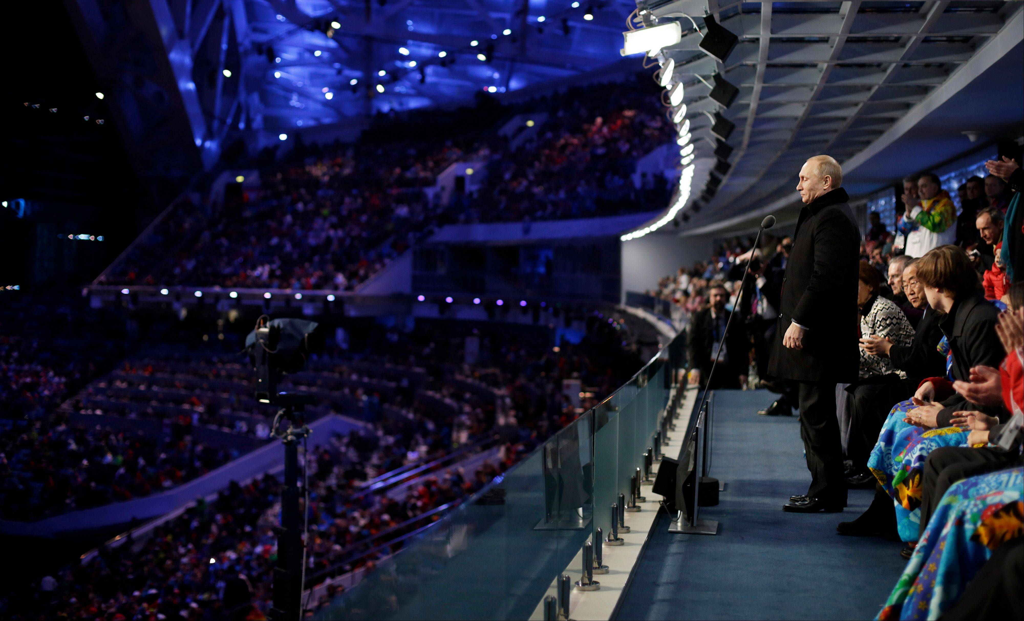 Russian President Vladimir Putin, right, stands to declare the 2014 Winter Olympics open.