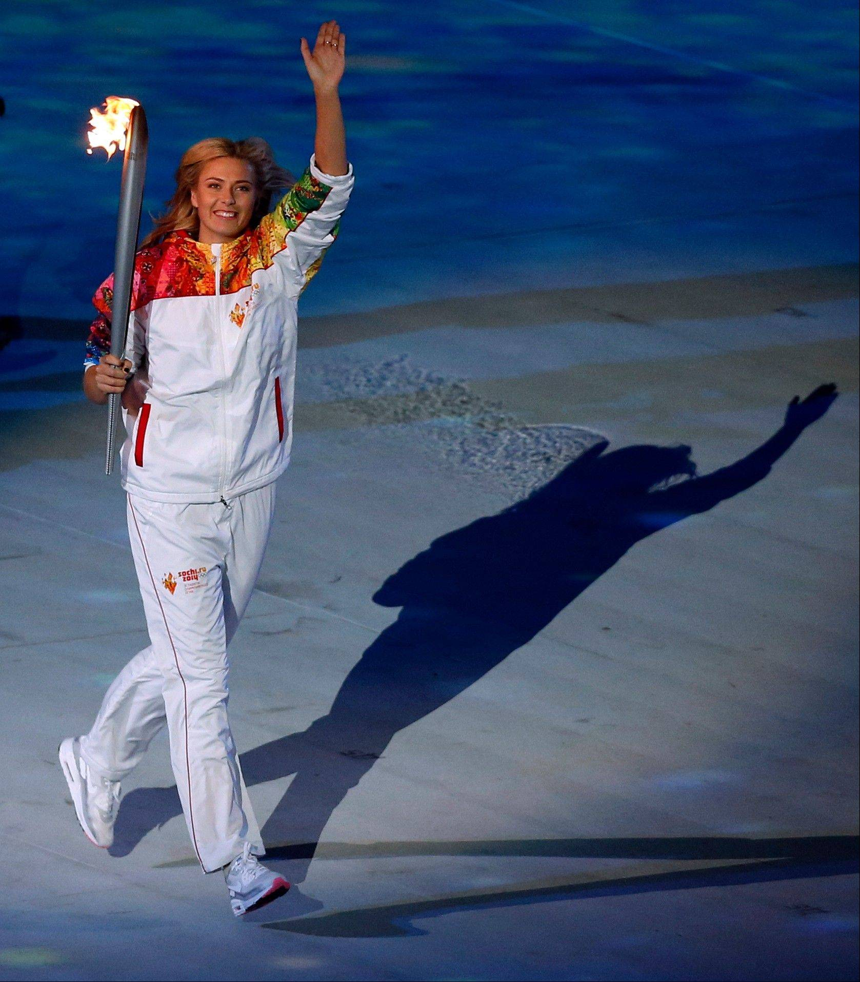 Maria Sharapova carries the torch during the opening ceremony.