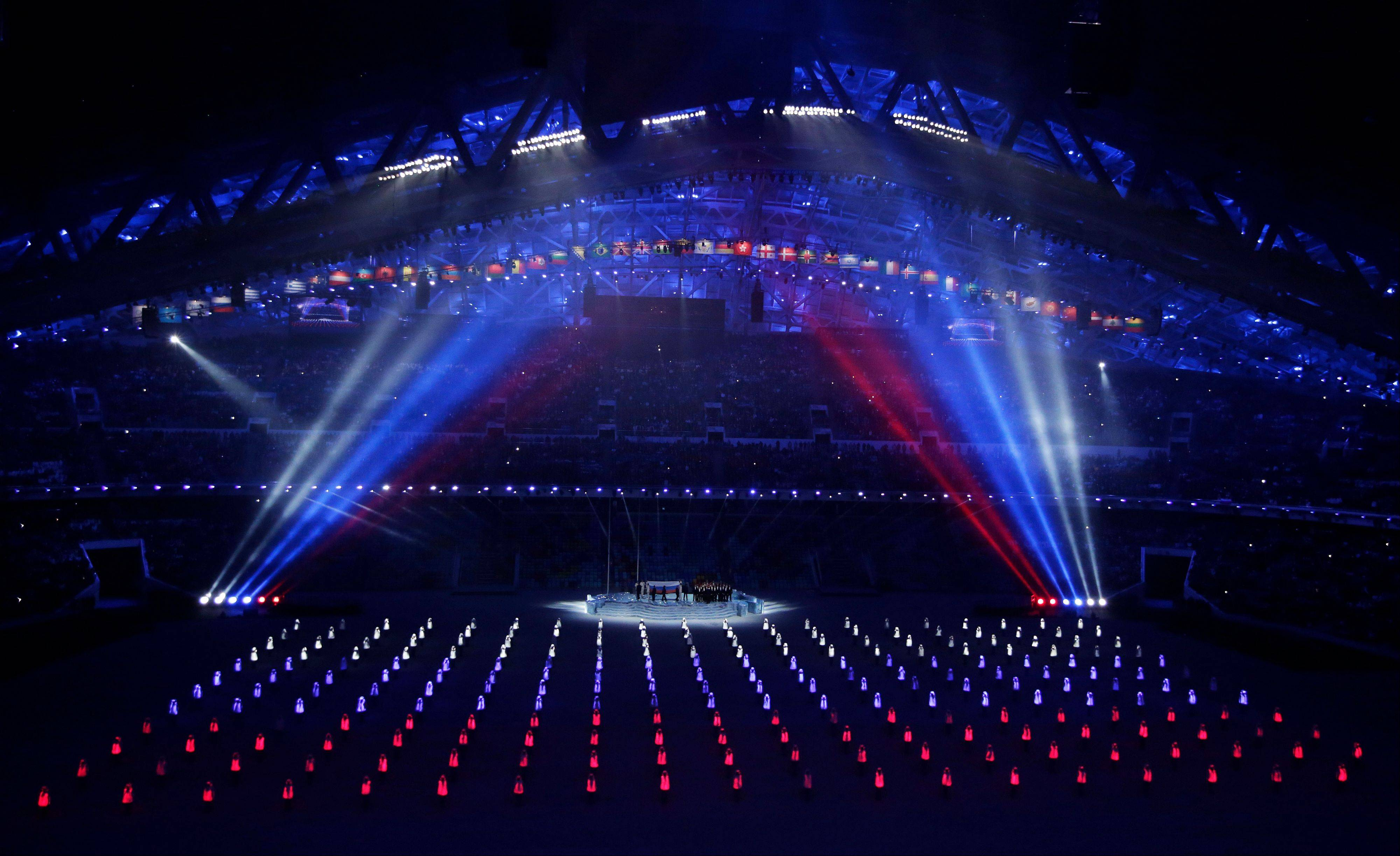 Performers wearing illuminated suits create the Russian flag during the opening ceremony.