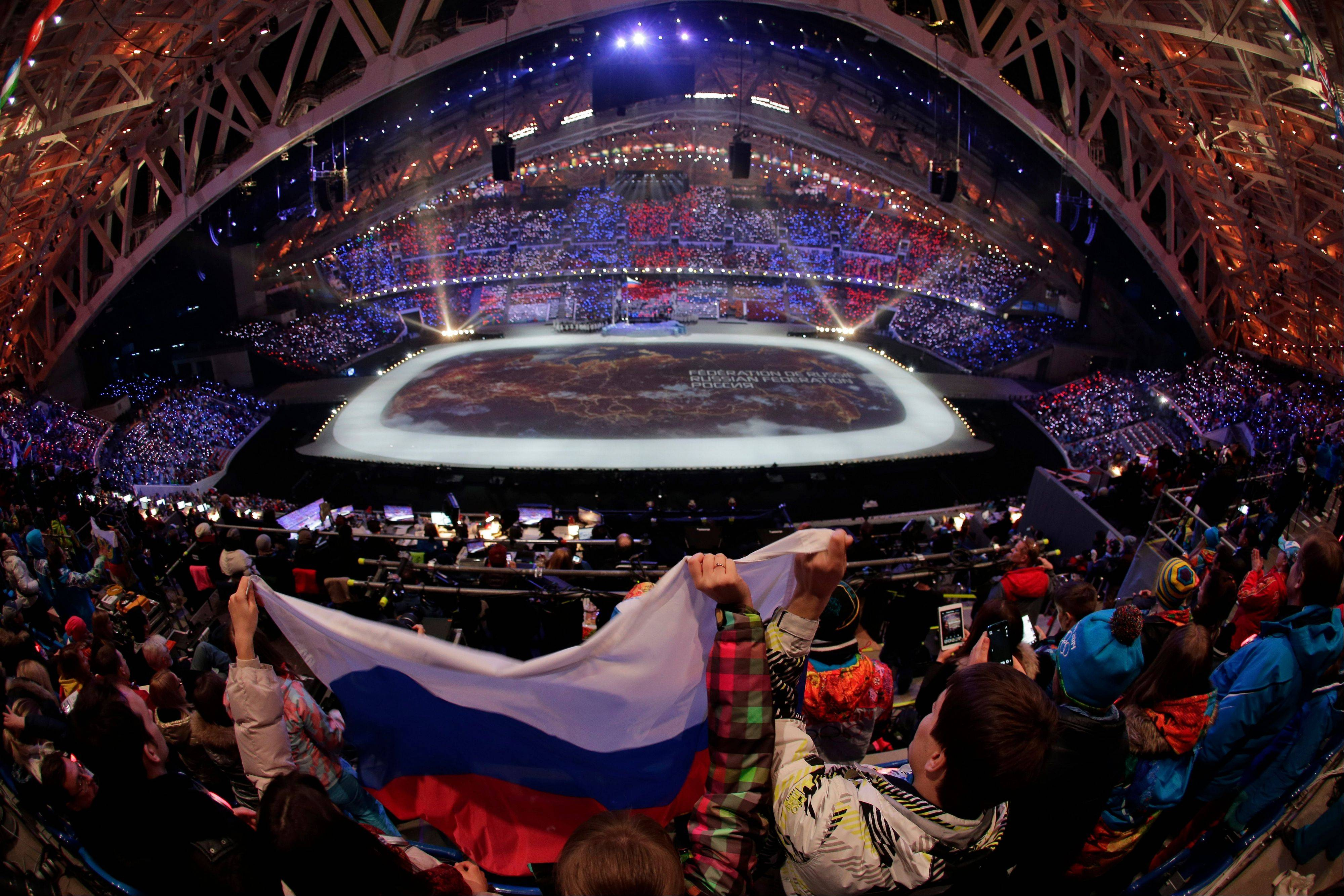 Spectators wave the Russian flag during the opening ceremony.