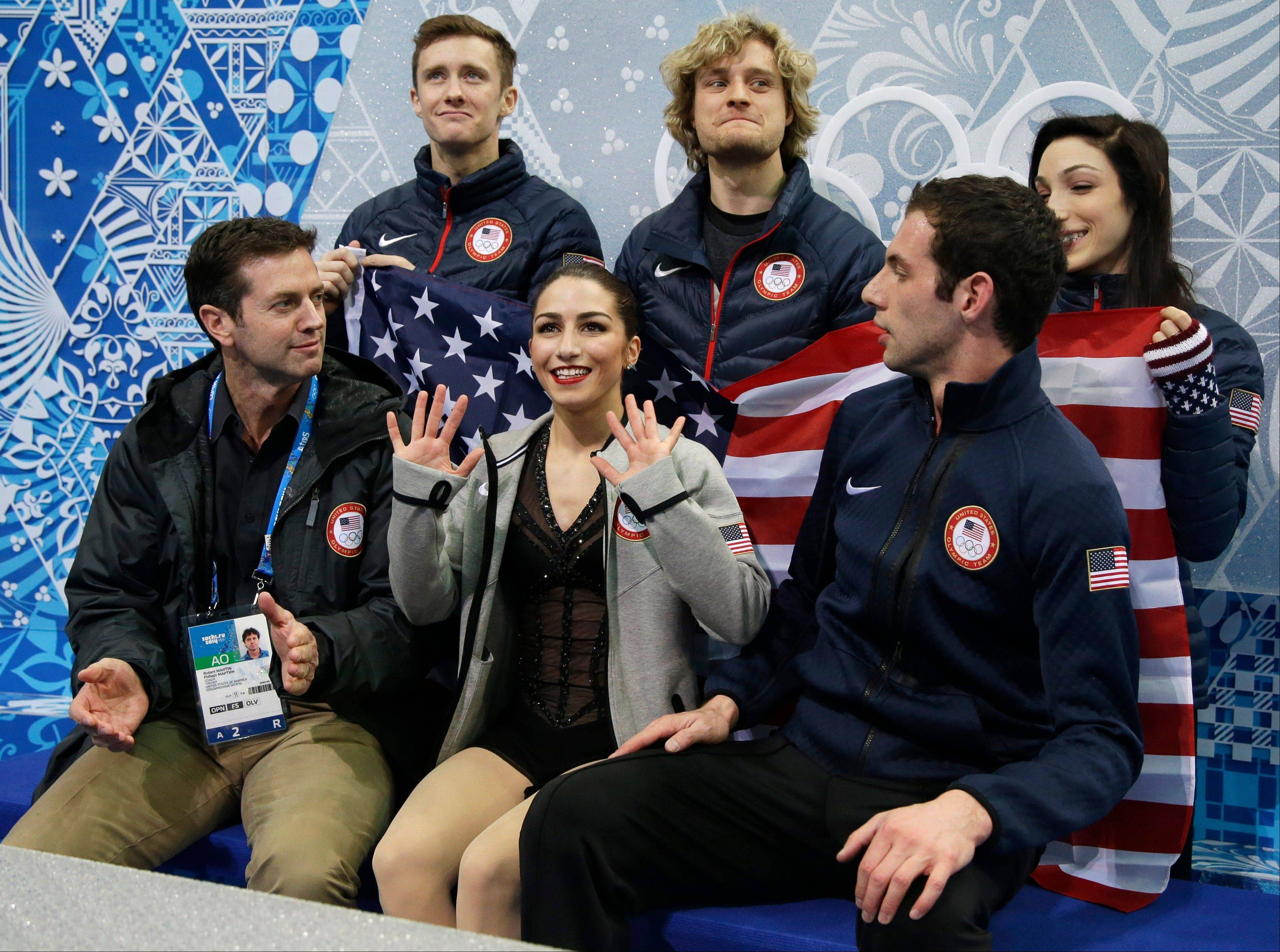 Marissa Castelli, center, and Simon Shnapir, right, wait for their results following the team pairs short program figure skating competition at the Iceberg Skating Palace Thursday during the 2014 Winter Olympics in Sochi, Russia.
