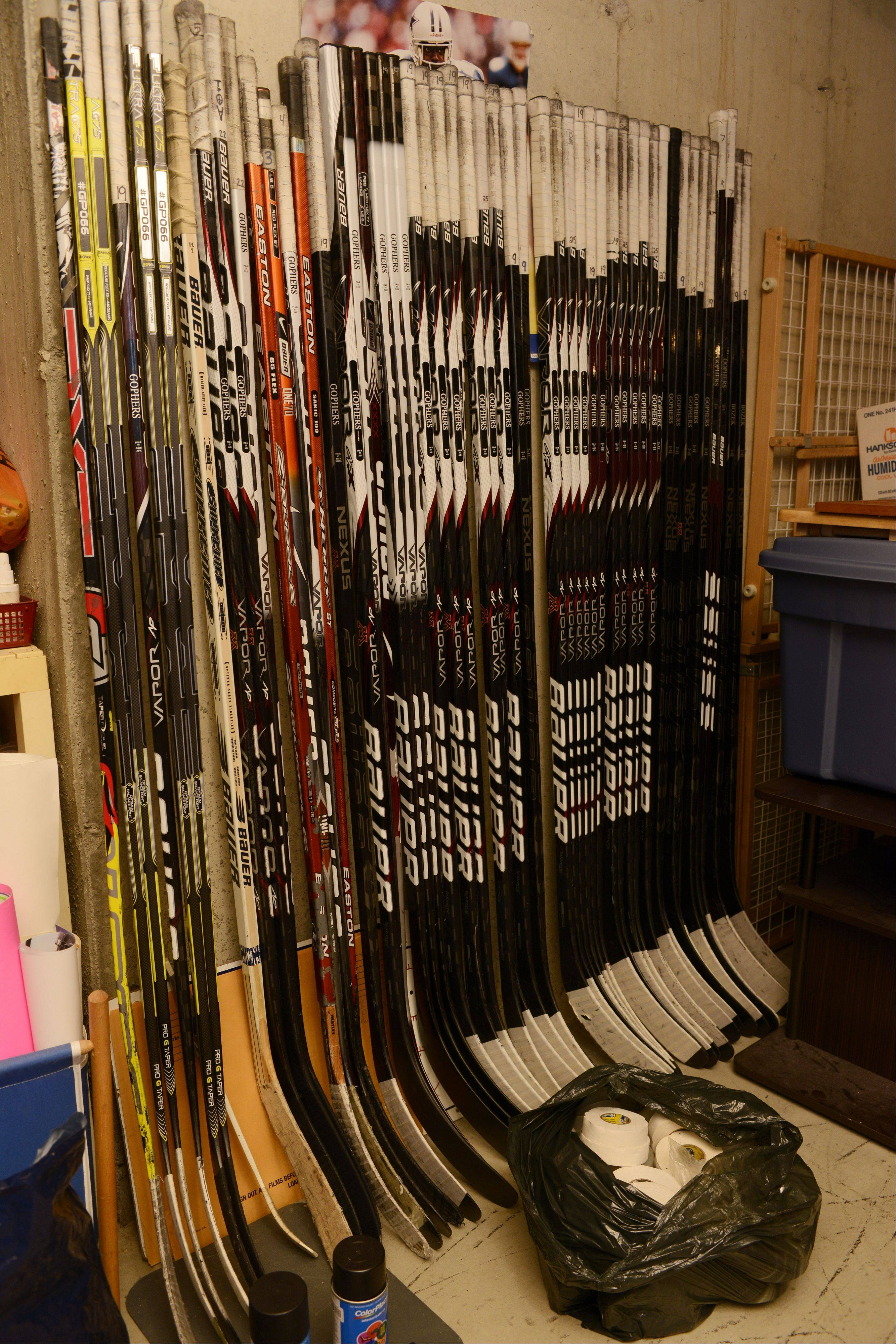 U.S. Olympic hockey player Megan Bozek's sticks line a wall of her parents' Buffalo Grove home. Her two older brothers also played hockey, and Megan developed her game at a young age.