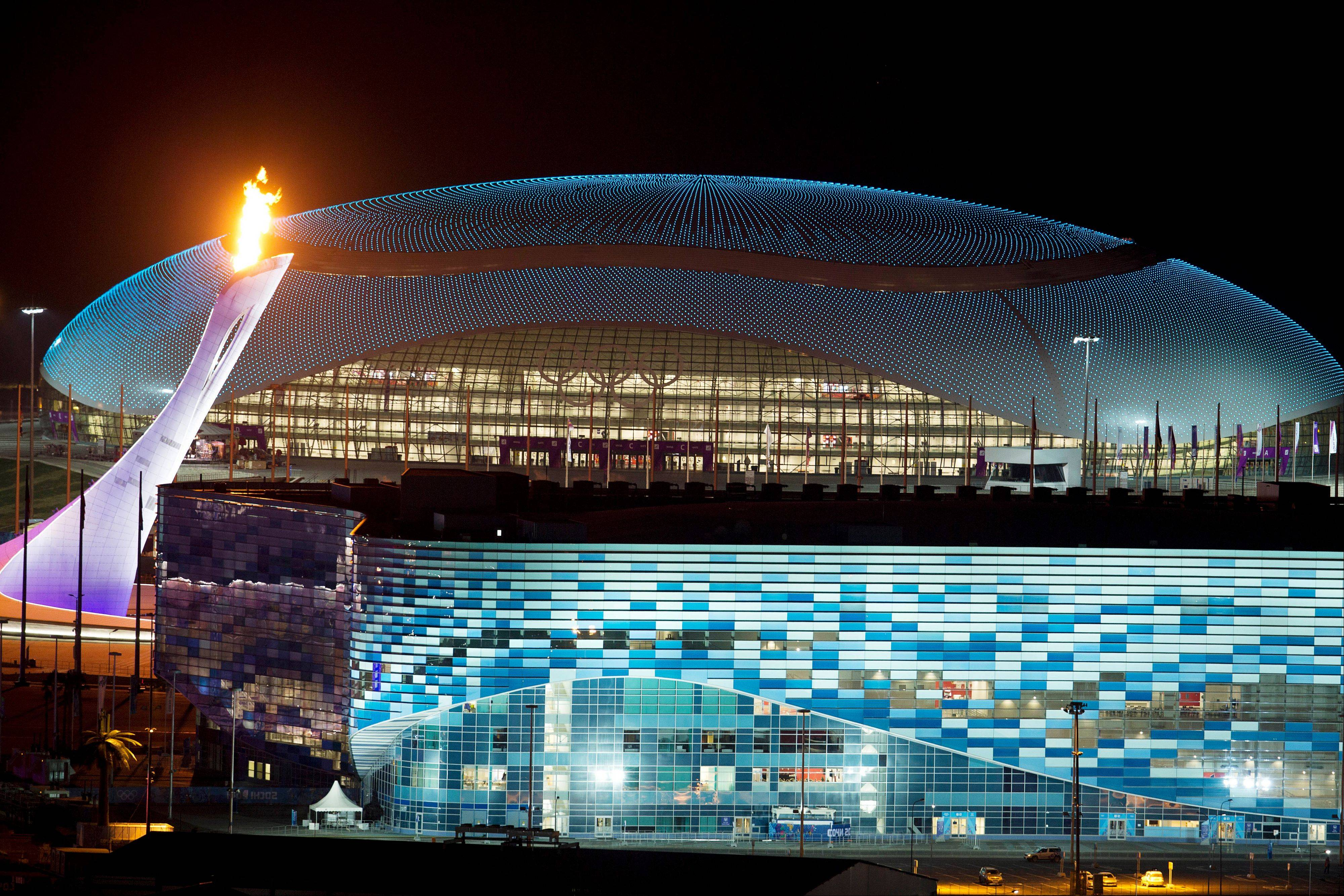 The Olympic Cauldron, left, is lit during a test between the Bolshoy Ice Dome, top, and the Iceberg Skating Palace, foreground, early Thursday morning, Feb. 6, 2014, in Sochi, Russia, prior to the start of the 2014 Winter Olympics.