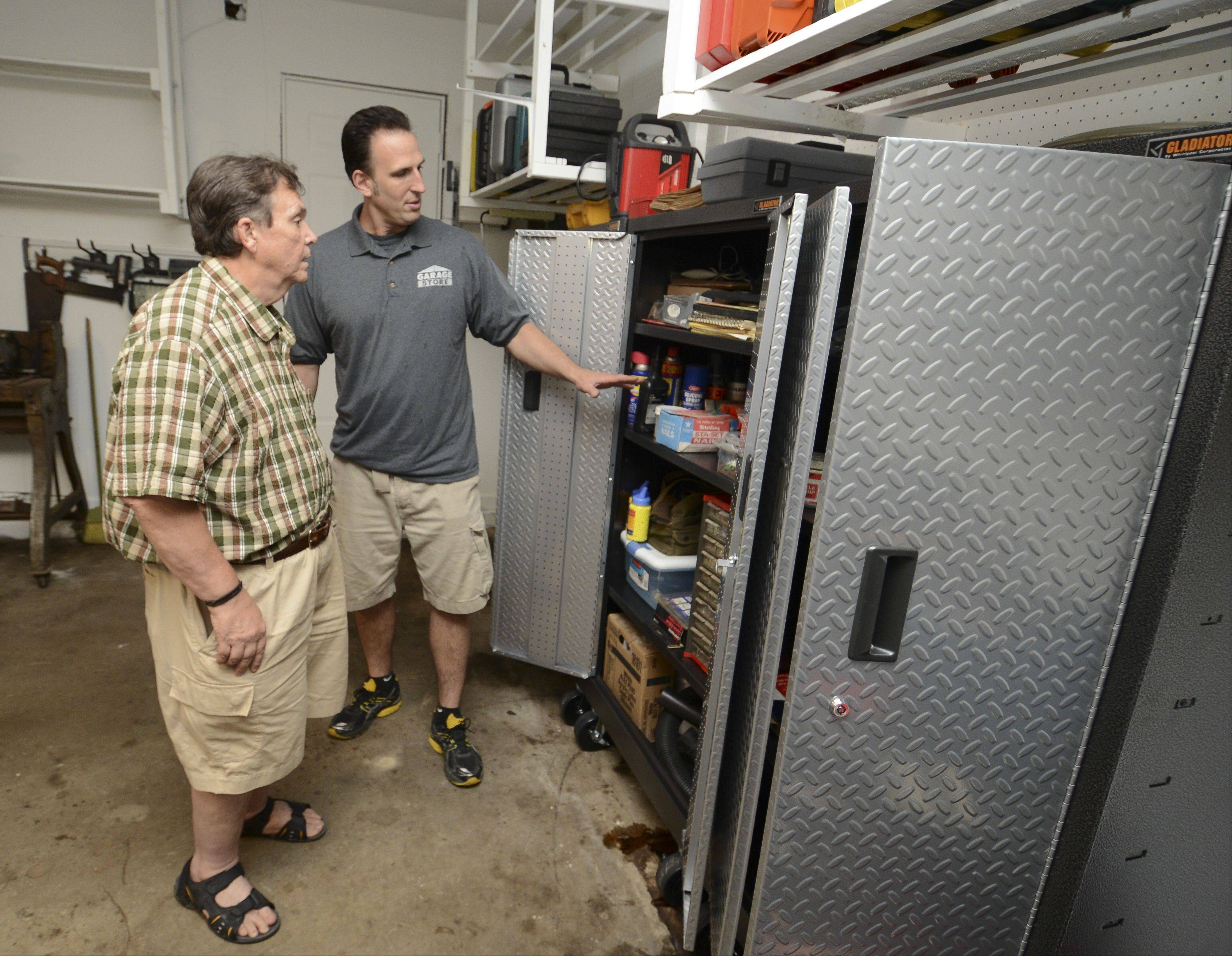 Jim Melchert of the Garage Store, right, shows the organization of new cabinets installed for Bob DeBellis of Roselle, winner of last year's Daily Herald Garage Makeover Giveaway.