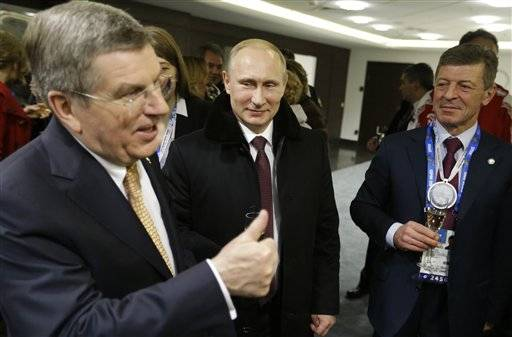 Russian President Vladimir Putin, center, talks with International Olympic Committee President Thomas Bach, left, and Deputy Prime Minister Dmitry Kozak, right, in the presidential lounge following the opening ceremony of the 2014 Winter Olympics, Friday, Feb. 7, 2014, in Sochi, Russia.