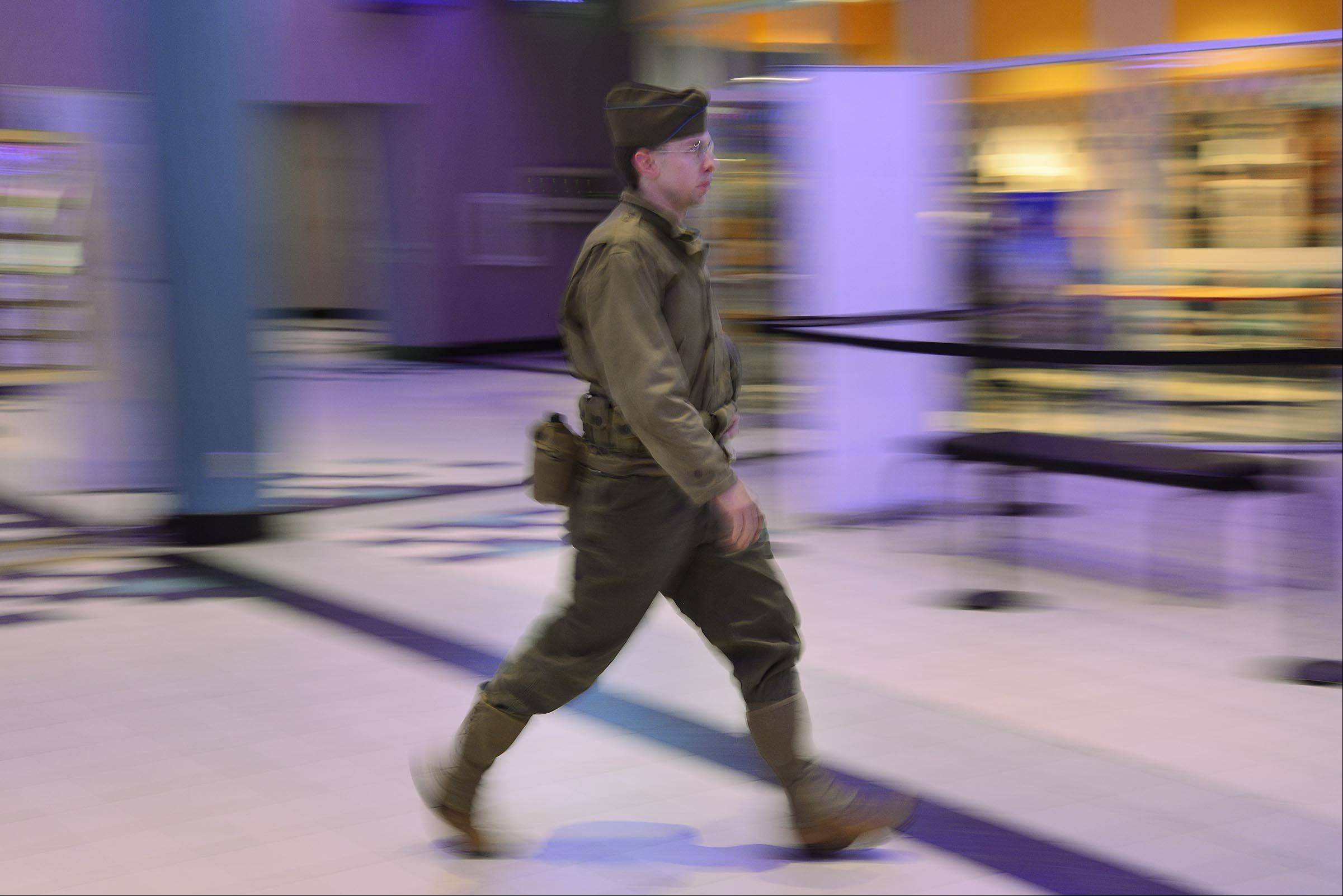 "In conjunction with the release of ""The Monuments Men,"" the WWII Historical Reenactment Society of Illinois/Indiana performed in the lobby of the Charlestowne 18 theaters in St. Charles Saturday. Mike Rickert of Romeoville marches across the lobby dressed as his grandfather, who was in the 9th Infantry and was one of the first soldiers to arrive in North Africa at the beginning of the war."