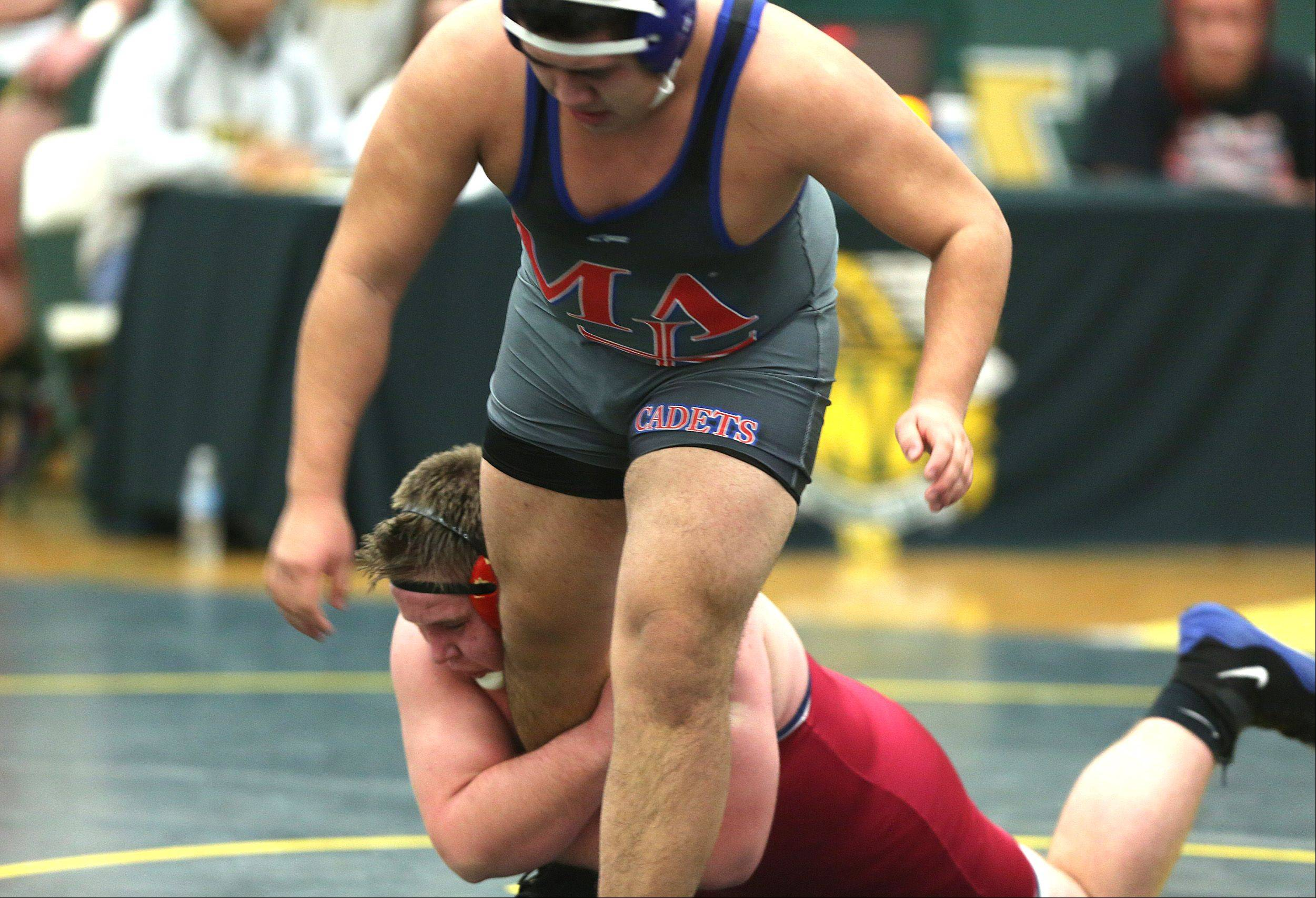 West Aurora's Sam Deisher grabs a hold of Marmion's Oscar Garza in the 285 pound class during regional wrestling at Waubonsie Valley High School.