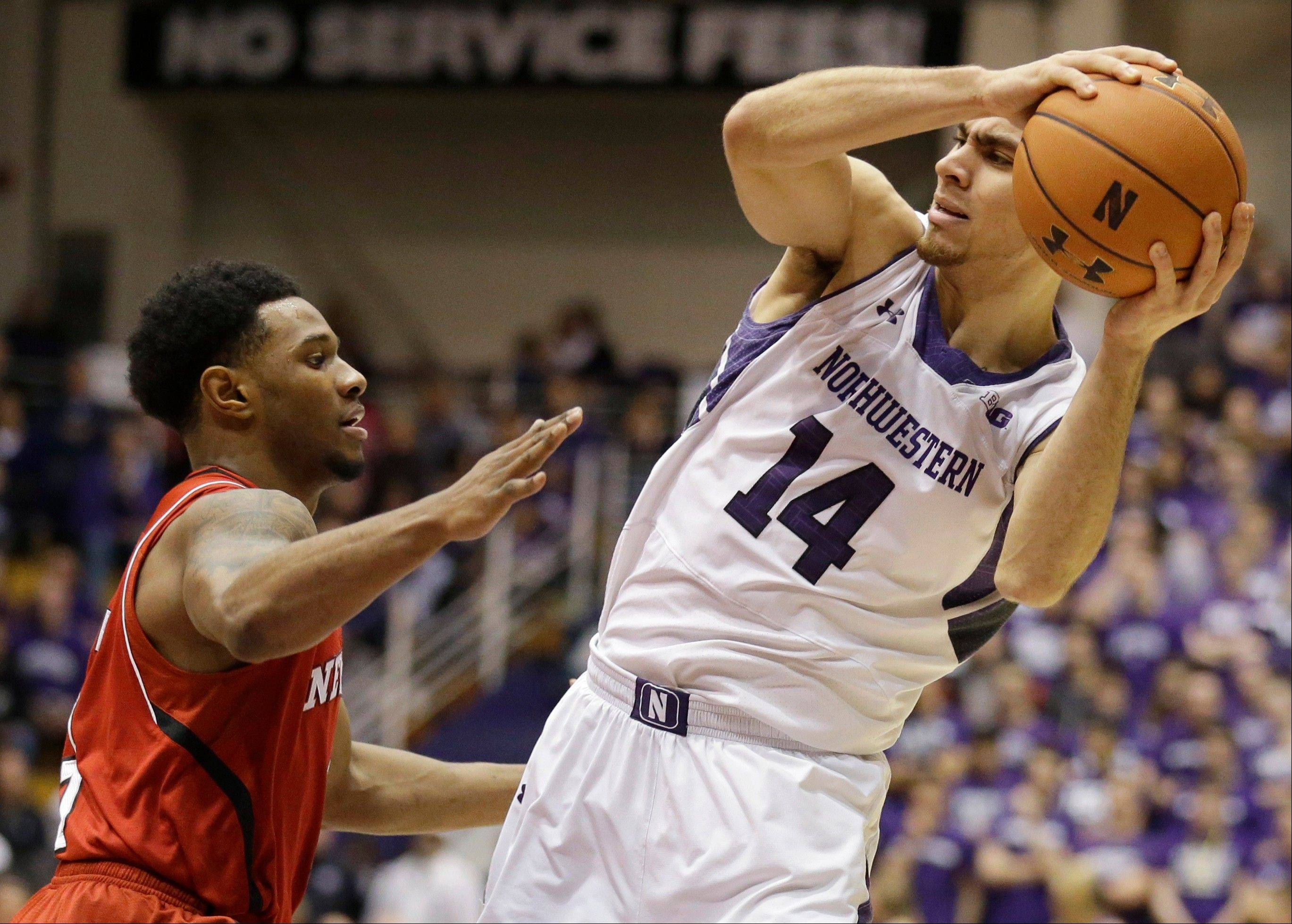 Northwestern guard Tre Demps, right, looks to a pass against Nebraska guard Benny Parker during the second half of an NCAA college basketball game in Evanston, Ill., on Saturday, Feb.8, 2014. Nebraska won 53-49. (AP Photo/Nam Y. Huh)