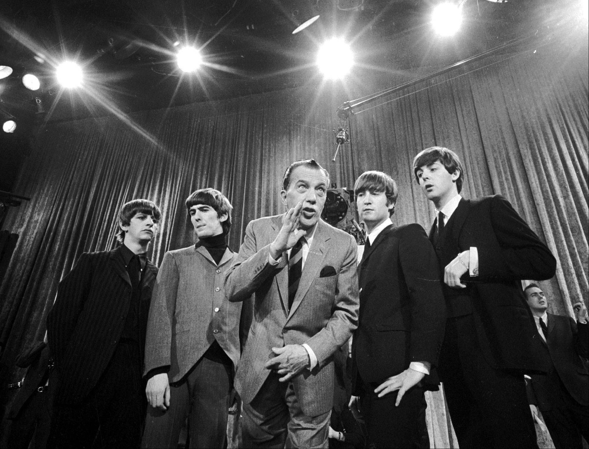 "In this Feb. 8, 1964 file photo, Ed Sullivan, center, stands with The Beatles, from left, Ringo Starr, George Harrison, John Lennon, and Paul McCartney, during a rehearsal for the British group's first American appearance, on the ""Ed Sullivan Show,"" in New York. The Beatles made their first appearance on ""The Ed Sullivan Show,"" America's must-see weekly variety show, on Sunday, Feb. 9, 1964. And officially kicked off Beatlemania."