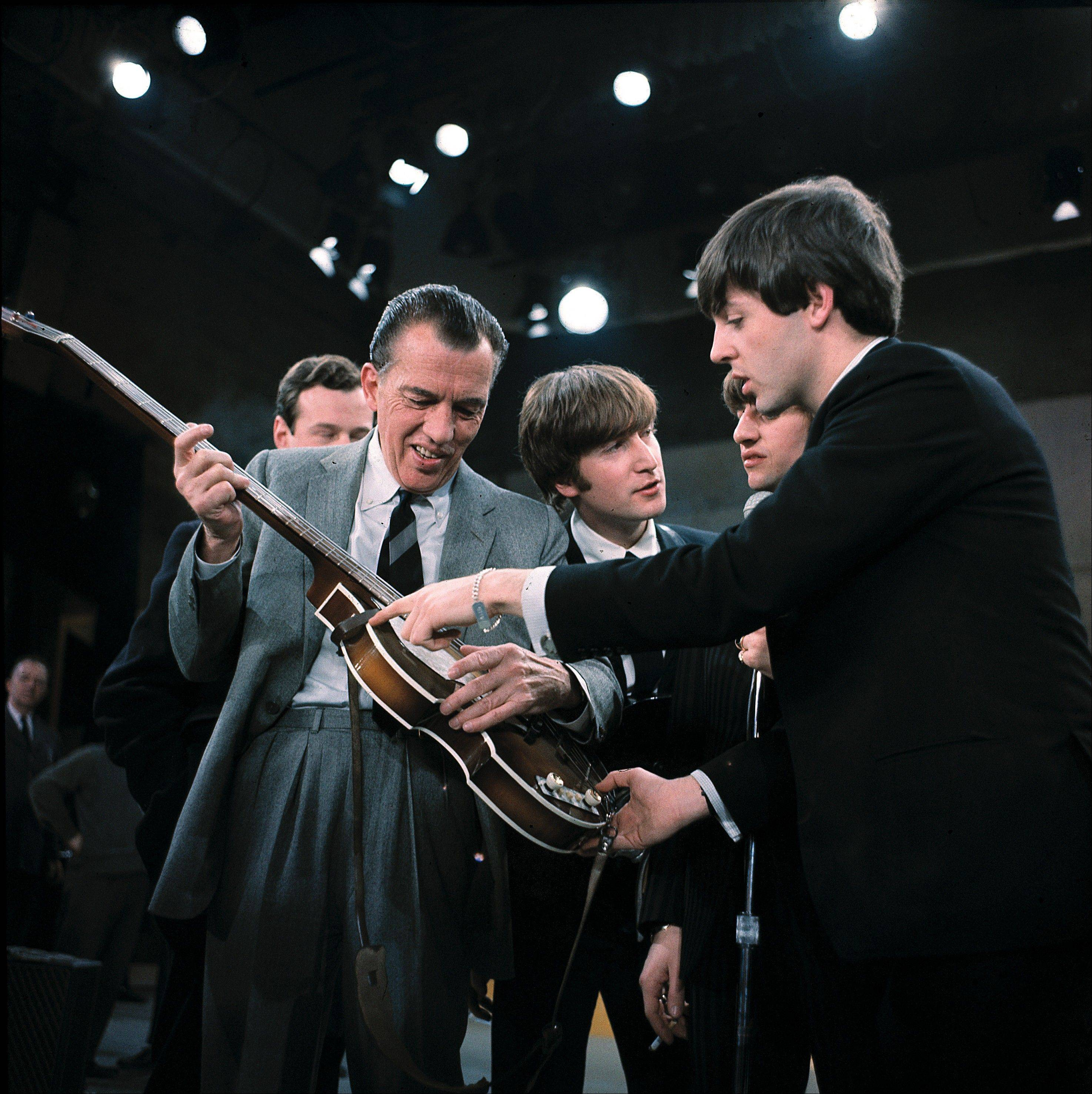 "In this Feb. 9, 1964 file photo, Paul McCartney, right, shows his guitar to host Ed Sullivan before the Beatles' live television appearance on ""The Ed Sullivan Show"" in New York. The Beatles made their first appearance on ""The Ed Sullivan Show,"" America's must-see weekly variety show, on Sunday, Feb. 9, 1964. And officially kicked off Beatlemania."