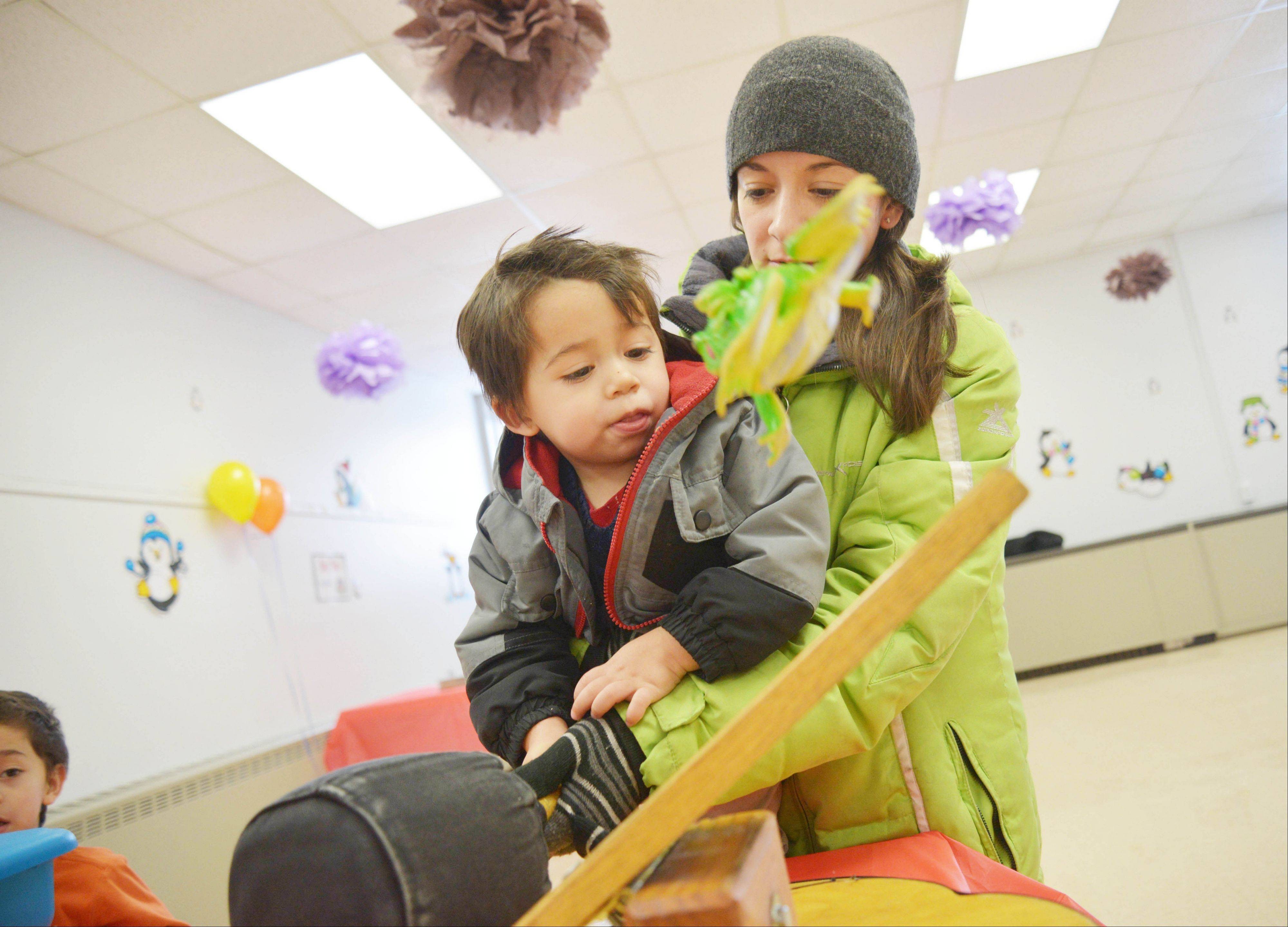 Kristy DaCanay and her son Caleb, 2, of Lombard, play the frog toss game at the Lombard Park District's annual Winter Carnival at Sunset Knoll Recreation Center Saturday.