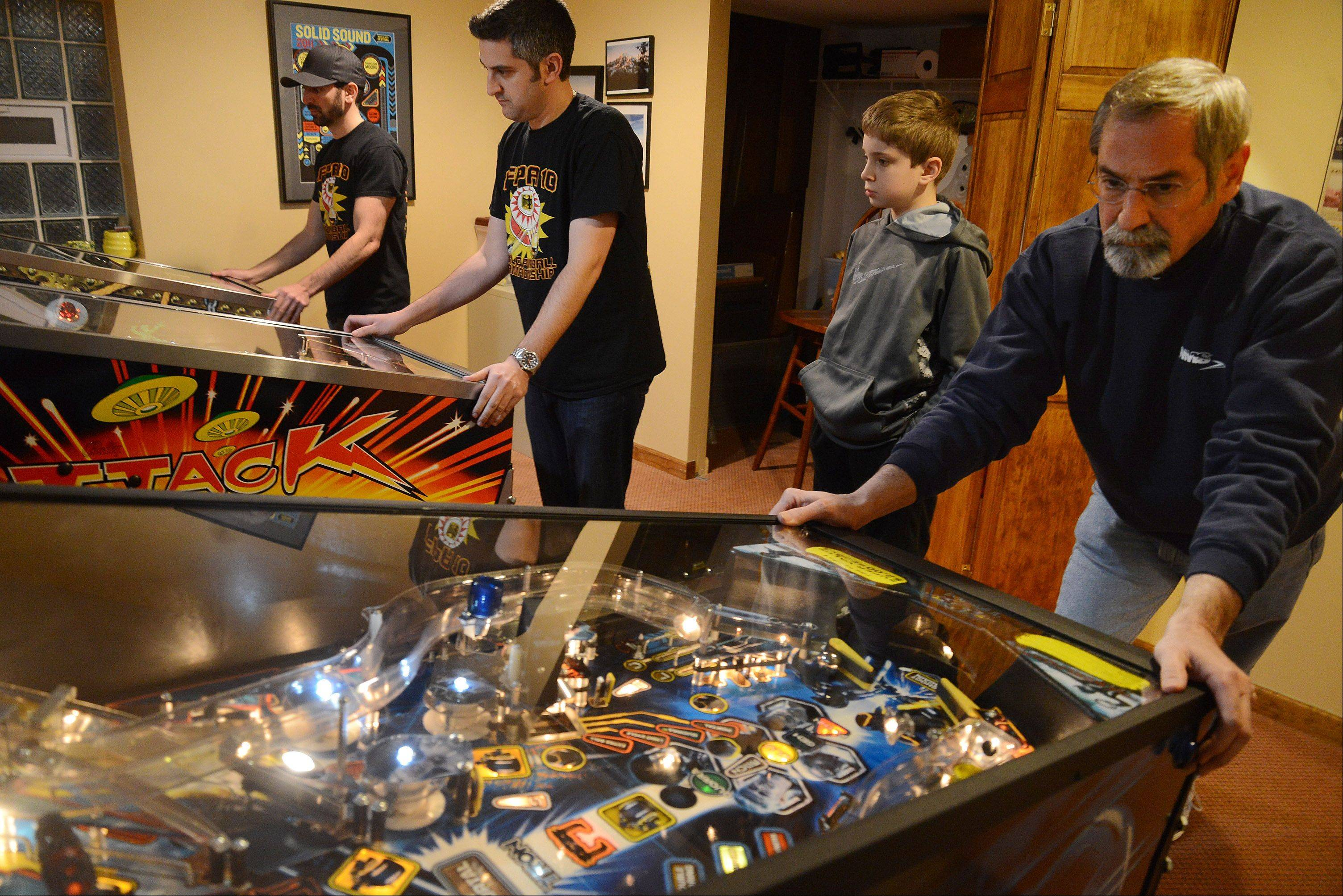Matthew Hooper, center, watches as the family Sharpe, from left, Zach, Josh and dad Roger work the pinball machines Saturday at the International Flipper Pinball Association tournament in Lincolnshire.