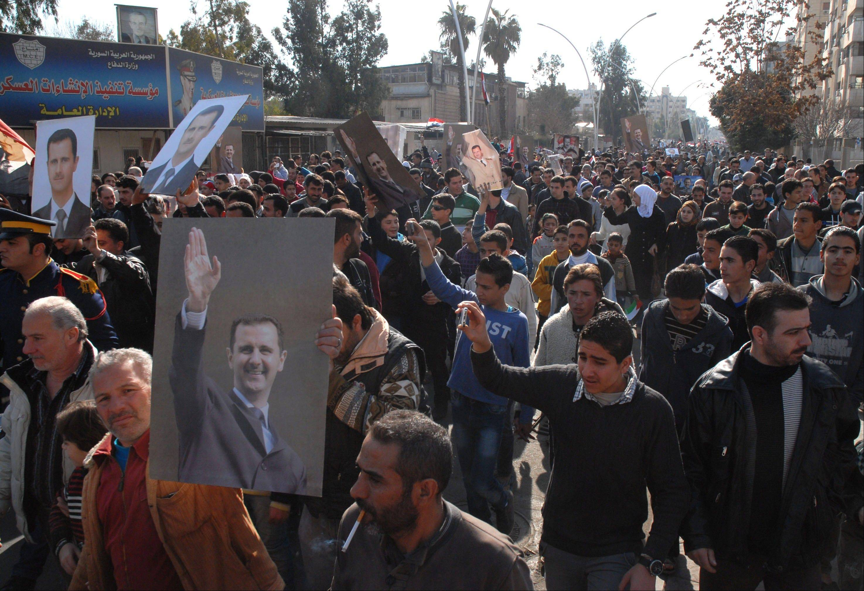 Pro-government Syrian protesters hold portraits of Syrian President Bashar Assad as they march during a demonstration at Kafar Souseh neighborhood Friday in Damascus, Syria.