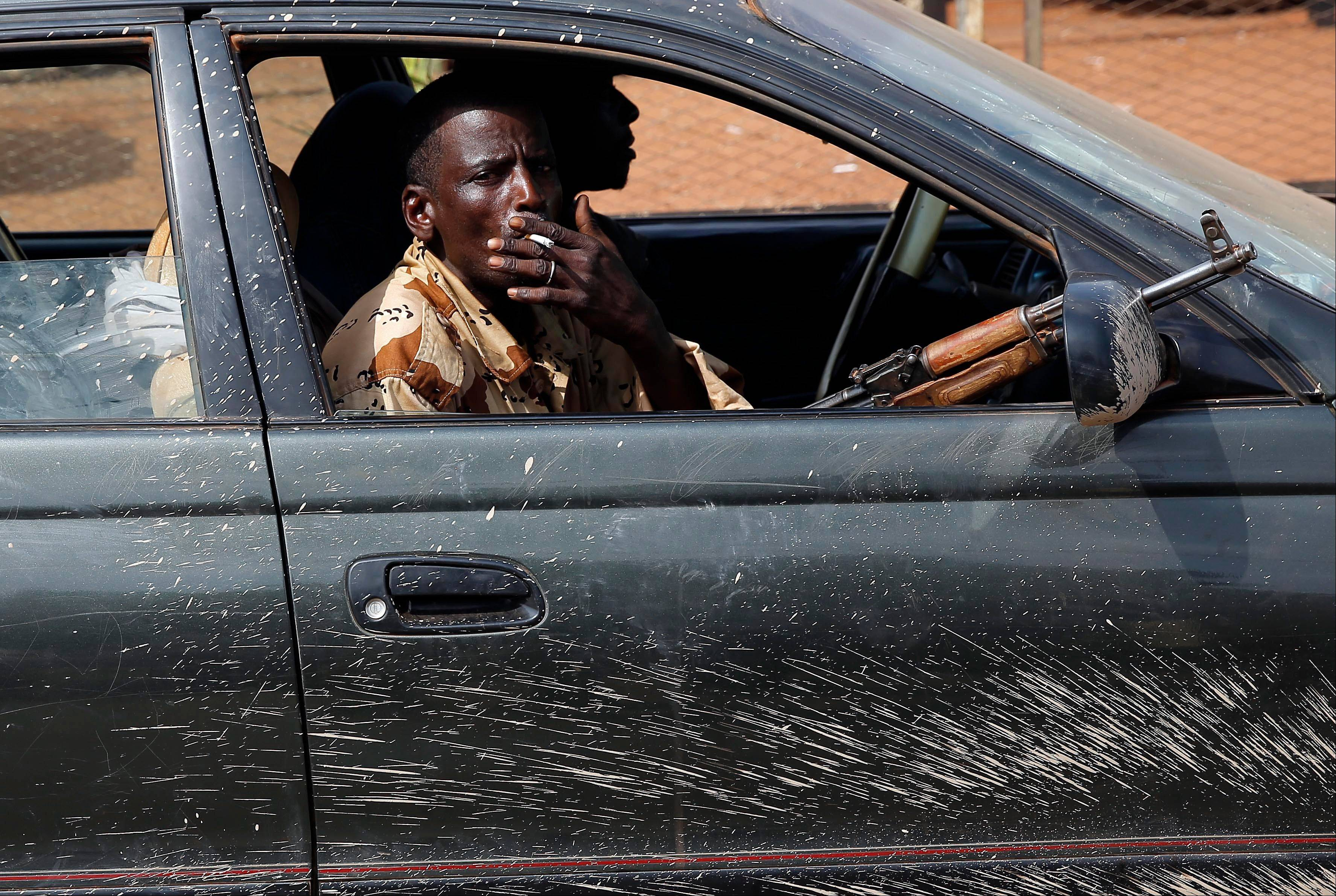 At PK12, the last checkpoint at the exit of the town, armed men drive Friday with thousands of Muslim residents from Bangui and Mbaiki fleeing the Central African Republic capital Bangui in a mass exodus.