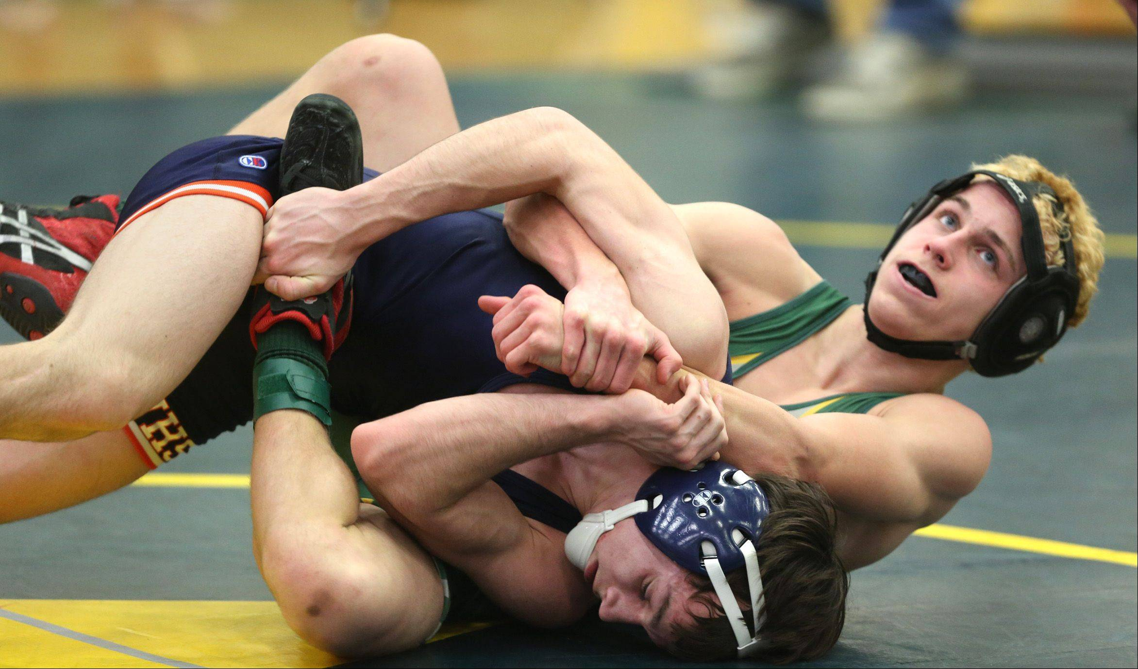 Naperville North's Aaron Kruk, left, is in the grasp of Waubonsie Valley's Michael Scalgione during regional wrestling at Waubonsie Valley High School.