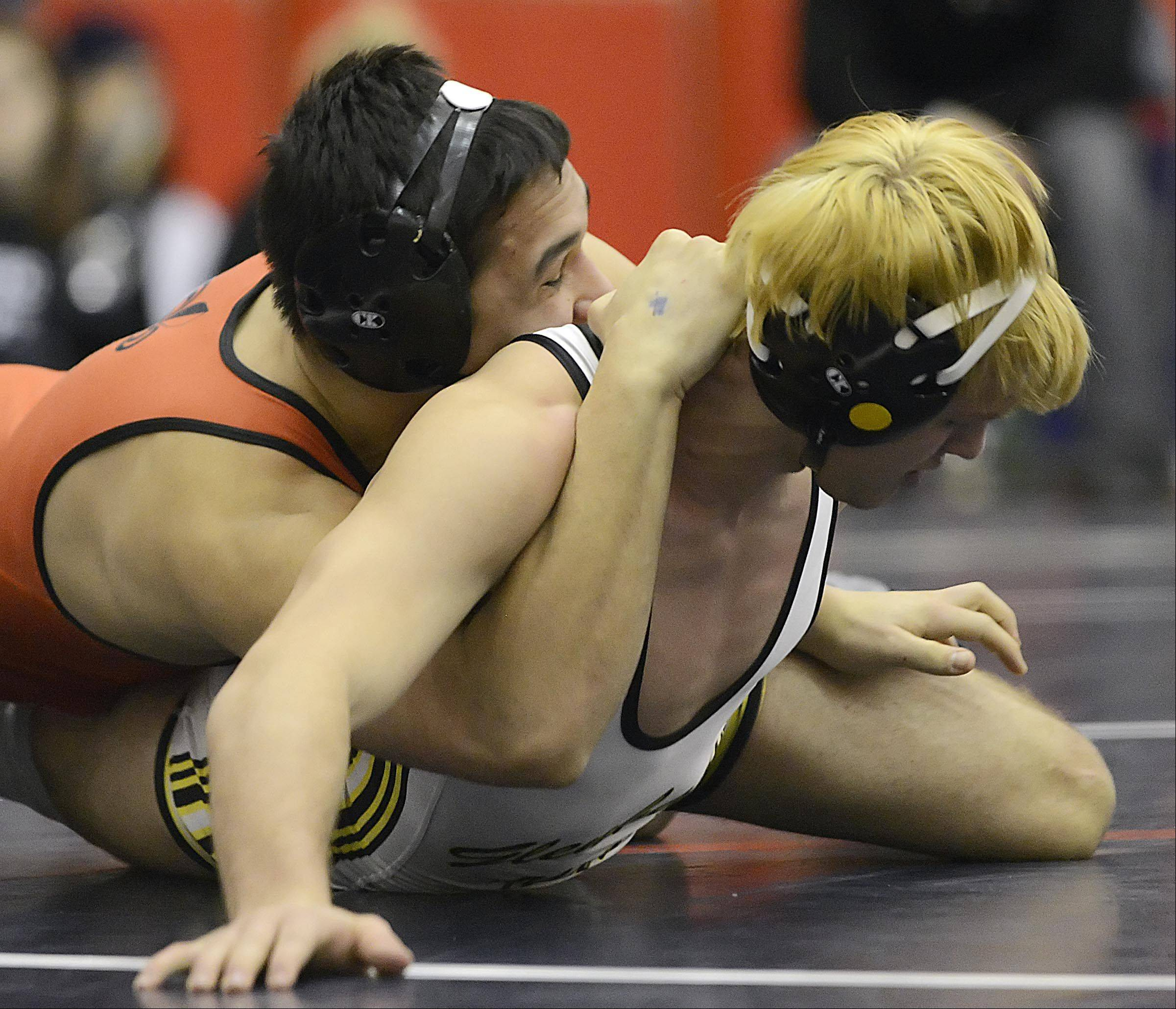 St. Charles East's Keone Derain tries a half nelson on Glenbard North's Anthony DePrima in the 152-pound weight class Saturday at the South Elgin regional wrestling tournament. Keone won the title by fall.