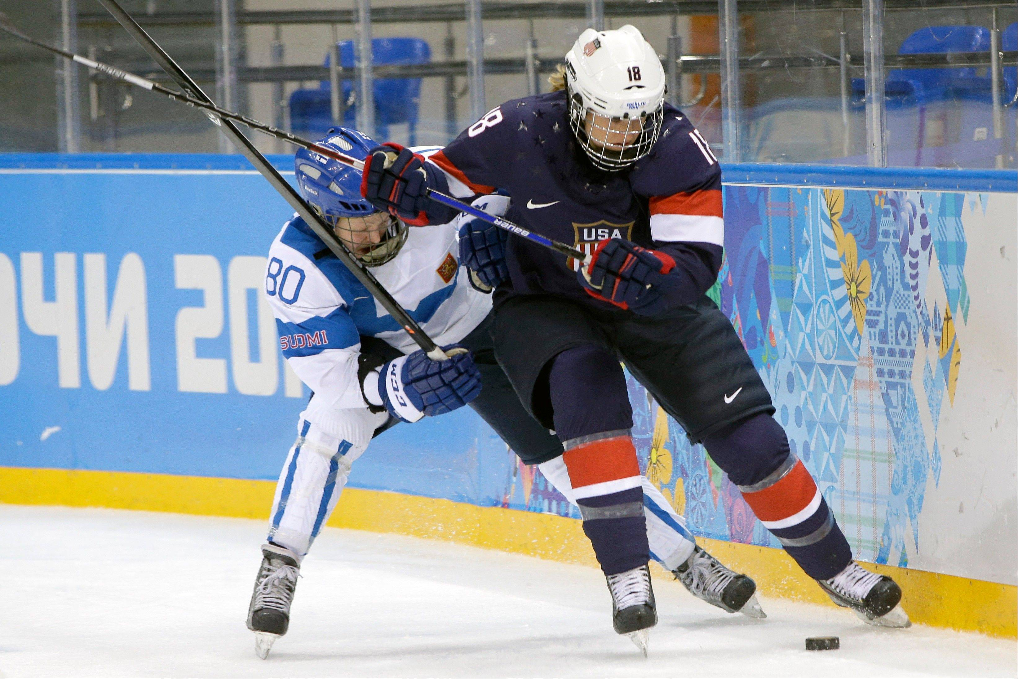 Tea Villila of Finland and Lyndsey Fry of the United States battle for control of the puck behind the net during the third period of the women's ice hockey game at the Shayba Arena during the 2014 Winter Olympics, Saturday, Feb. 8, 2014, in Sochi, Russia.