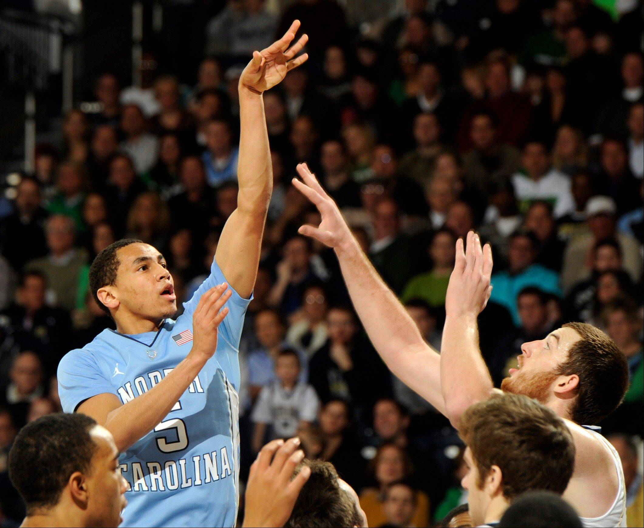 North Carolina guard Marcus Paige, left, puts up a shot over Notre Dame forward Garrick Sherman during the second half of an NCAA college basketball game Saturday, Feb. 8, 2014, in South Bend, Ind.