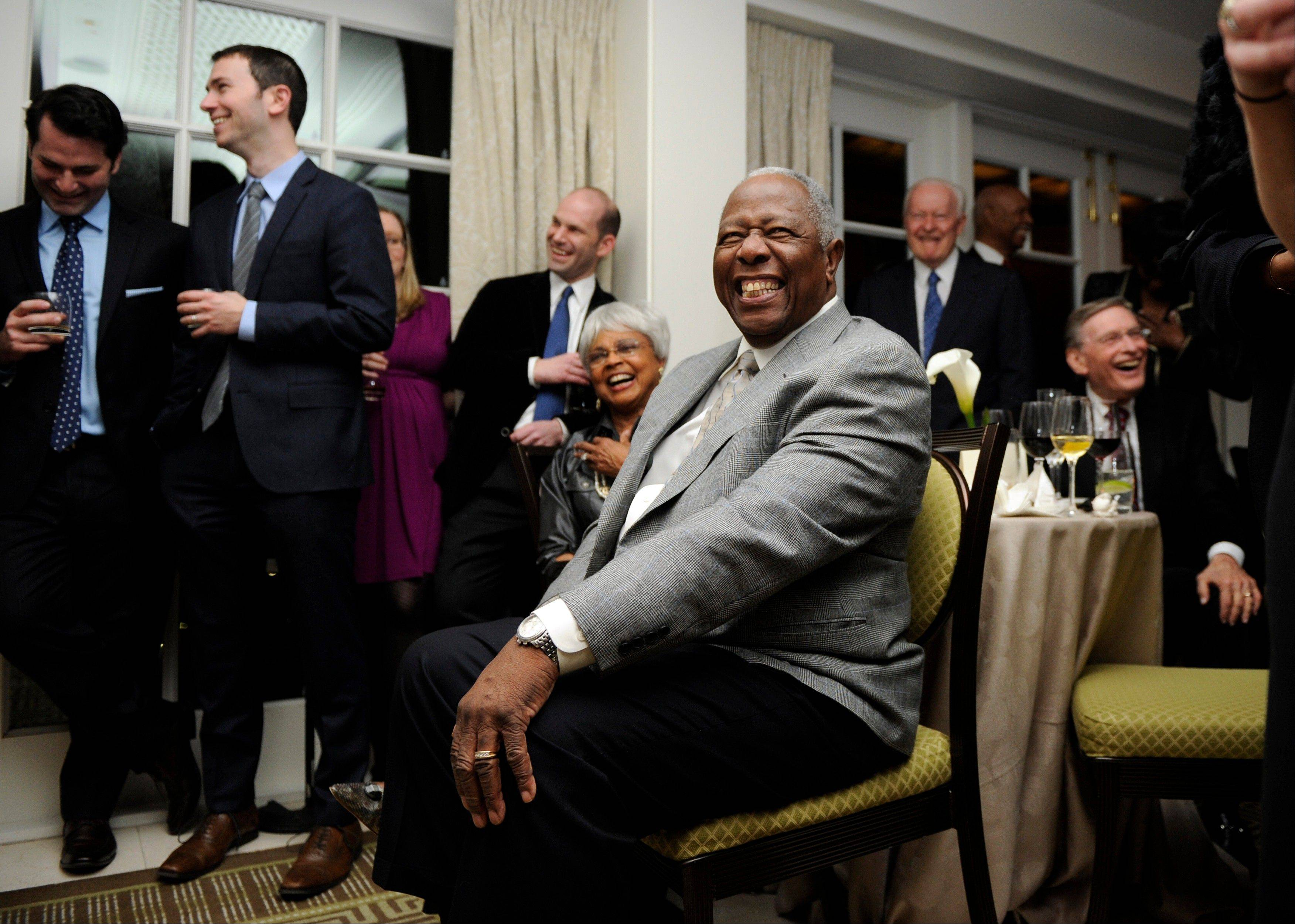 Baseball Hall of Famer Hank Aaron, center, smiles Friday during a reception in his honor.
