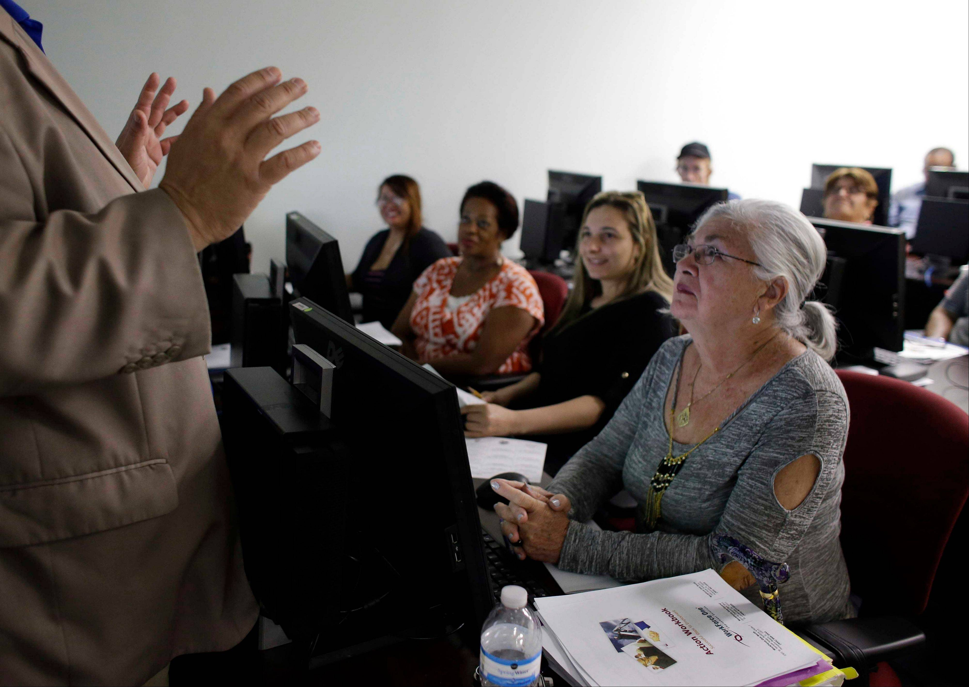 Rosi Pozzi, 73, of Davie, Fla., right, listens during a job search workshop at WorkForce One, in Davie, Fla. Two straight weak job reports have raised doubts about economists� predictions of breakout growth in 2014. The global economy is showing signs of slowing again.