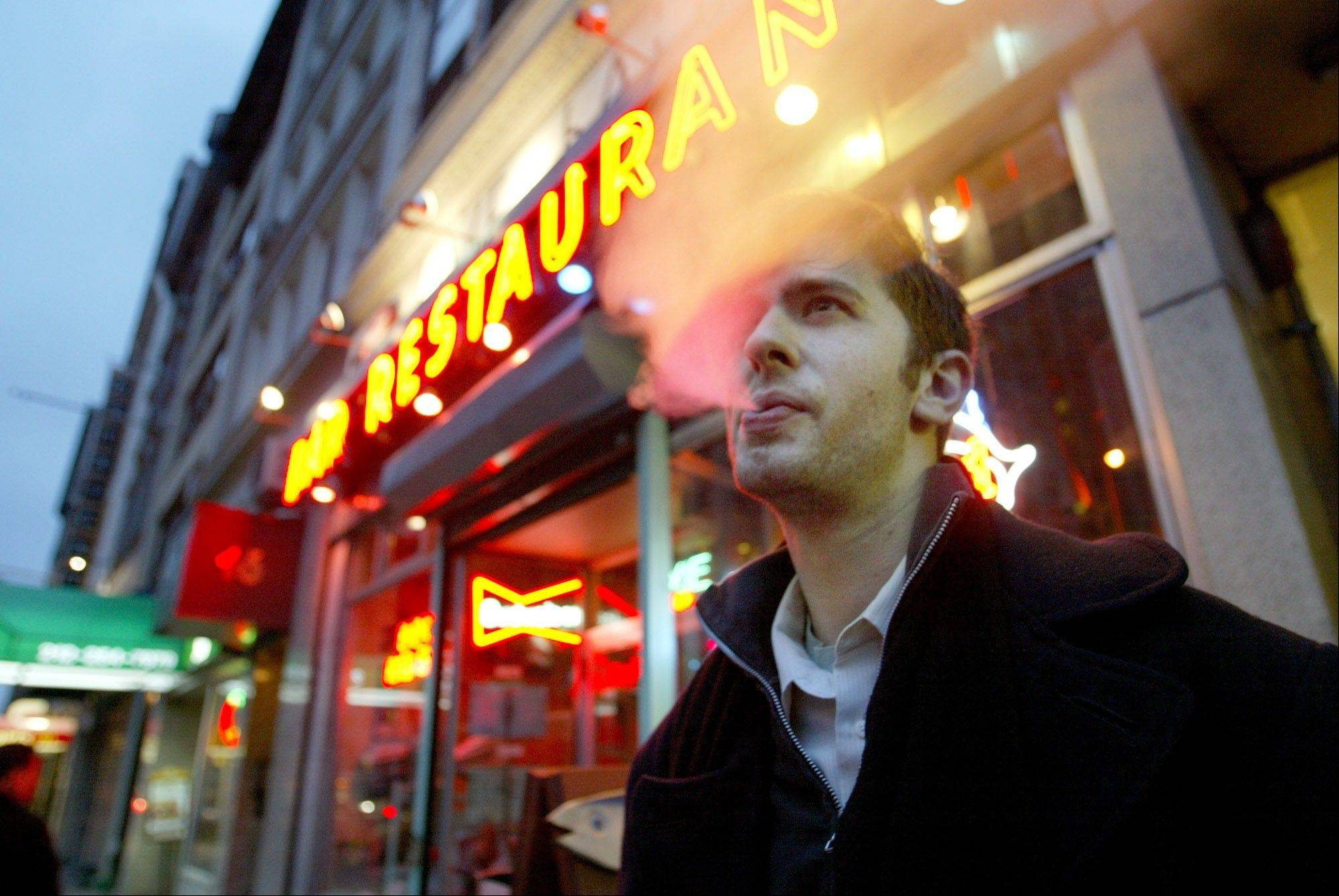 David Ozanich of Brooklyn smokes outside the Live Bait bar in New York after a city-wide ban on smoking in bars and restaurants went into effect.