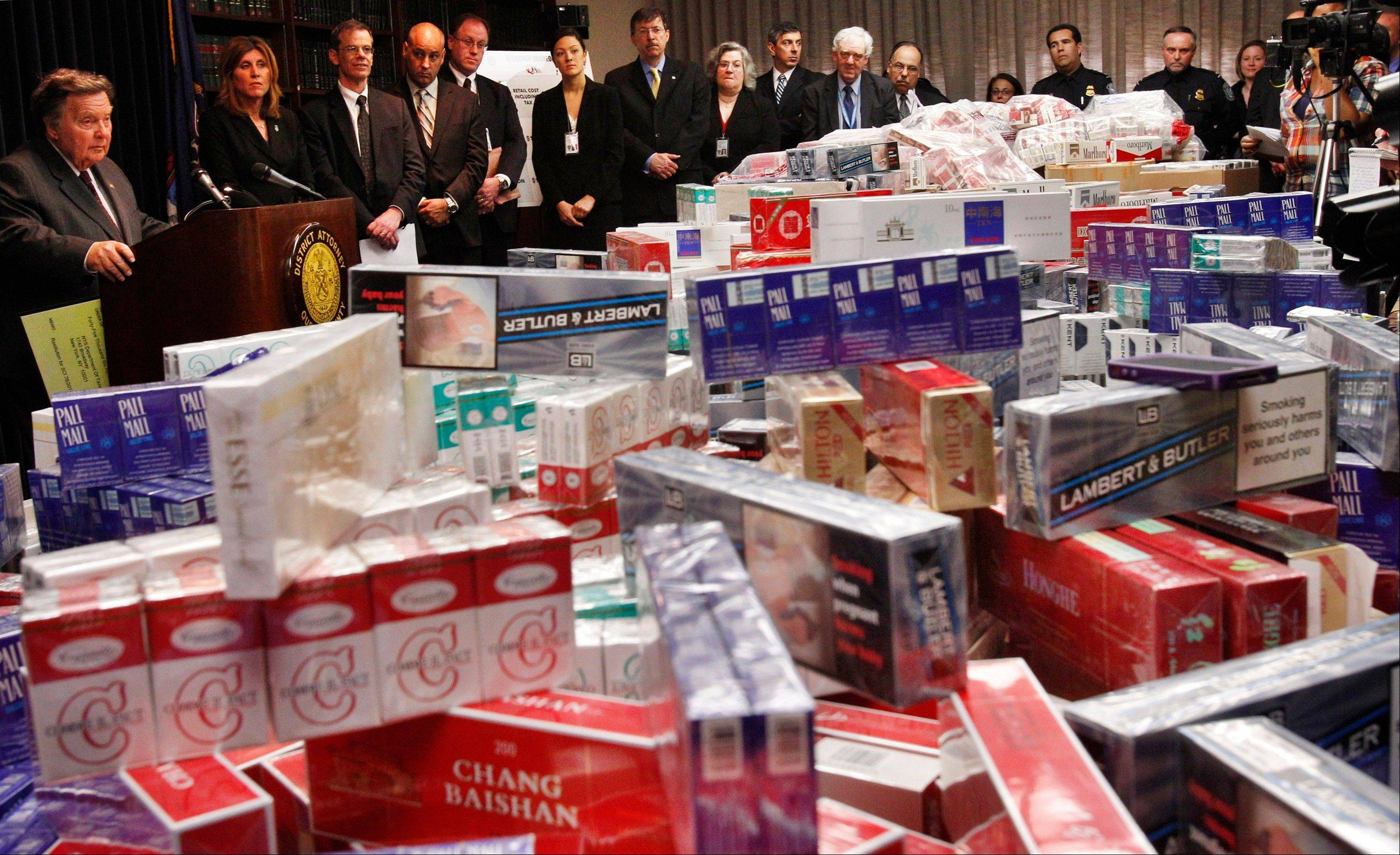 Queens District Attorney Richard Brown, left, joins state and federal officials in the Queens borough of New York to announce a crackdown on cigarette smugglers and tax evaders behind a display of cartons of confiscated cigarettes. Cigarette taxes have increased around the country. Though prices vary from state to state, on average a pack of cigarettes that would have sold for under $1.75 20 years ago would cost about $6 now.