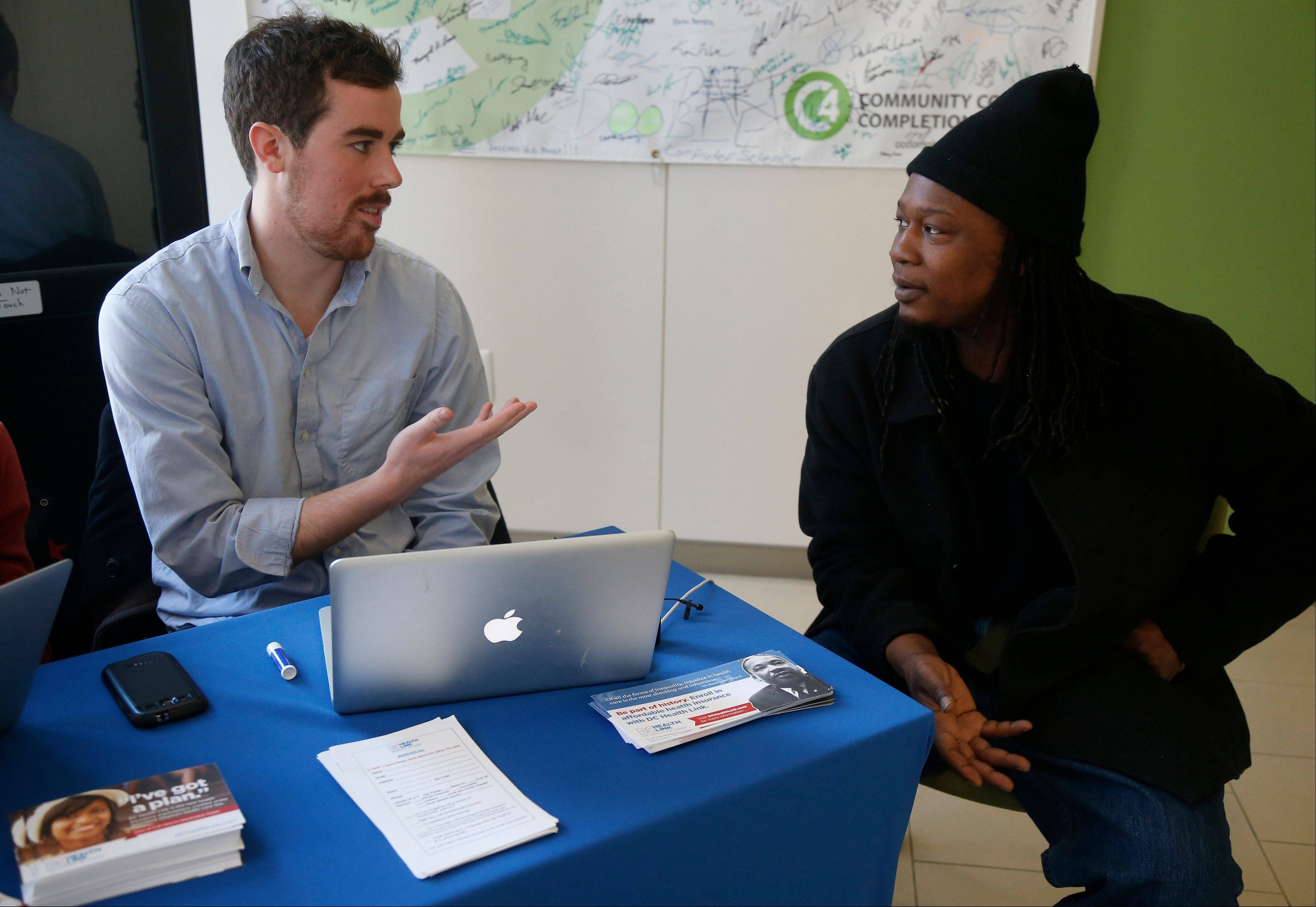 David Bransfield, a state outreach coordinator for Young Invincibles, a group which supports President Barack Obama's health care law, talks with student Philippe Komongnan, 27, who is in the process of signing up for health care, at the University of the District of Columbia in Washington.