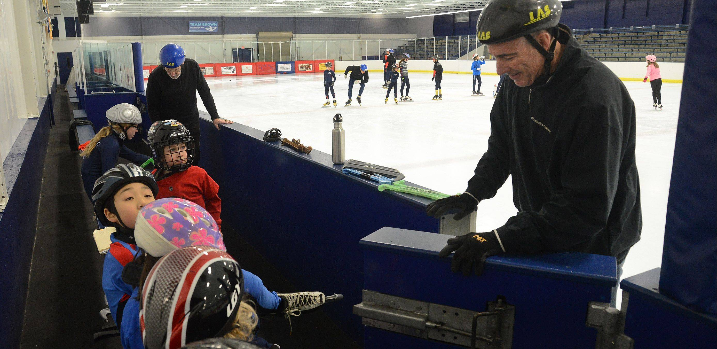 Coach David Mann, right, and two-time Olympic speed skater Chuck Burke, far left, work with the skaters during a practice with the Northbrook Speed Skating Club.