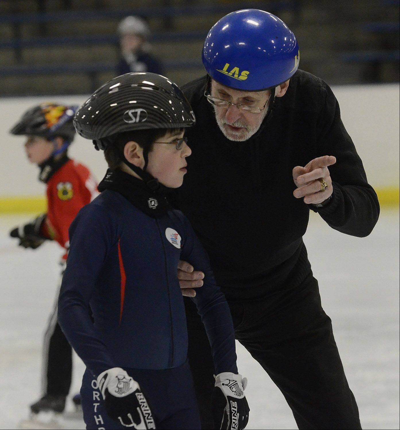 Olympic speed skater Chuck Burke, 82, of Northbrook, offers some advice to 9-year-old Reese Melsher during practice with the Northbrook Speed Skating Club last week.