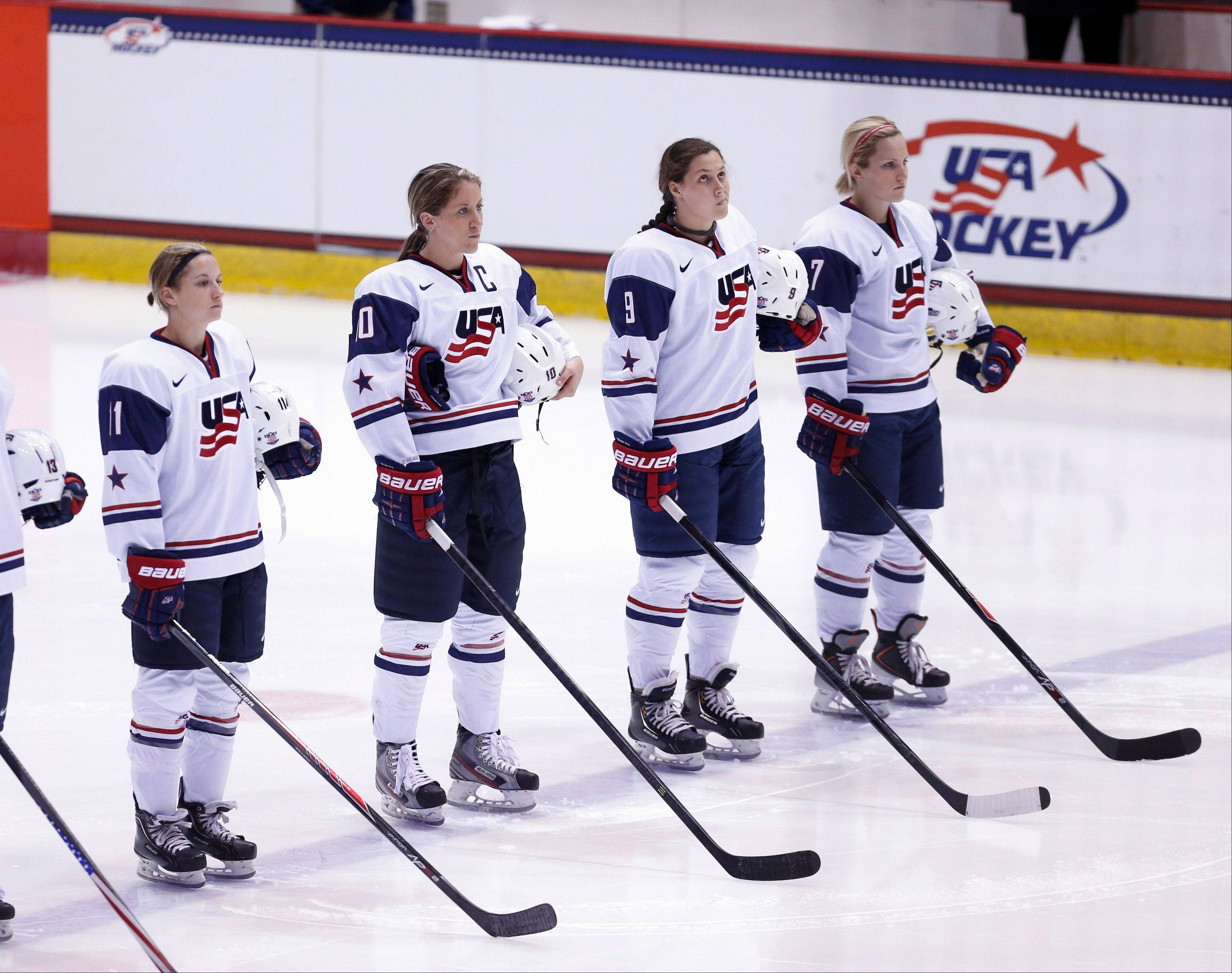 U.S. Women's Hockey Team member Megan Bozek, of Buffalo Grove, wearing jersey number 9, stands with her teammates during the national anthems before a Four Nations Cup women's hockey game against Sweden last November in Lake Placid, N.Y.