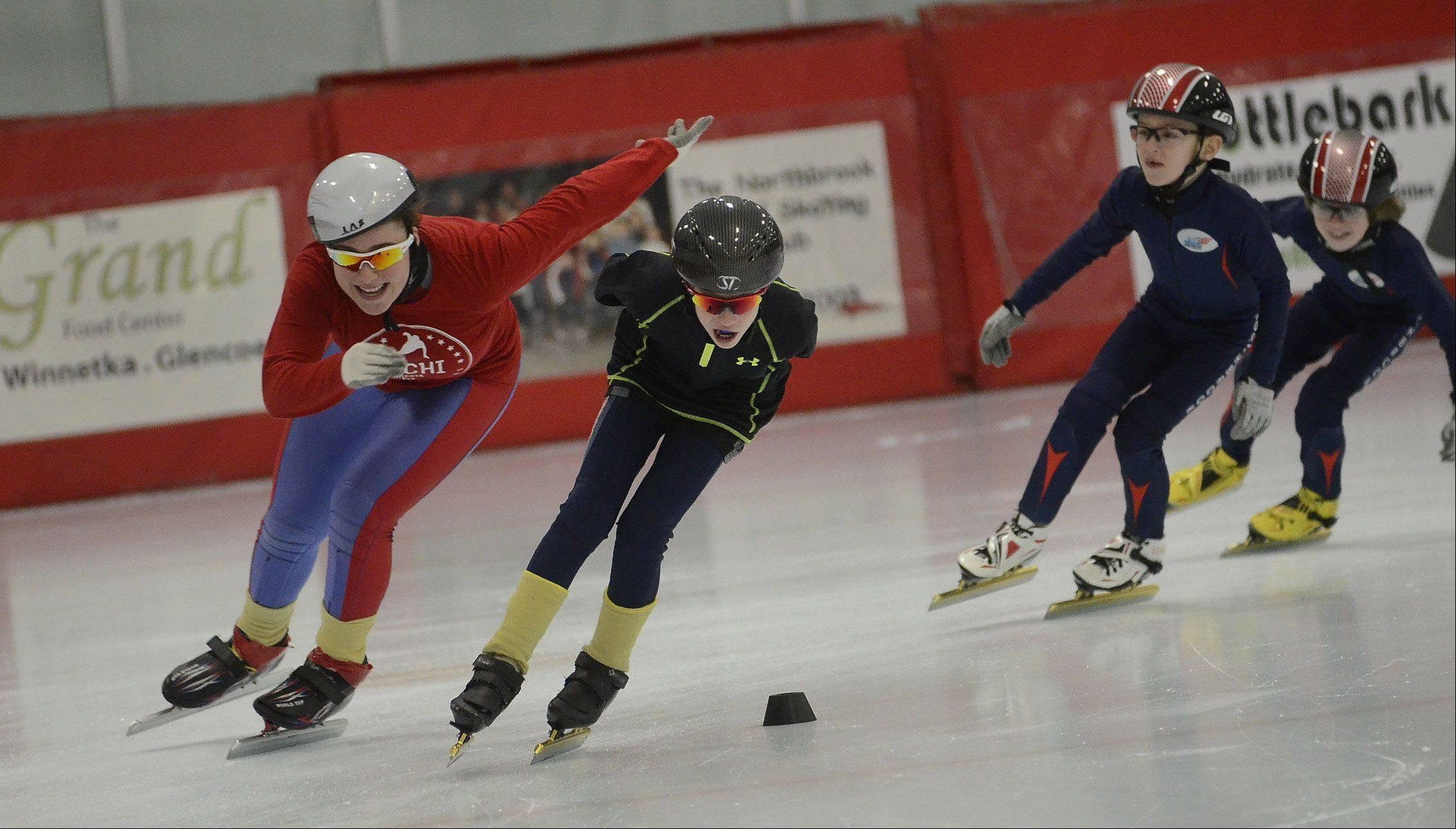 Simone Grach, left, and Carl Tatelli spin out of a turn while practicing with the Northbrook Speed Skating Club last week at the Northbrook Sports Center.