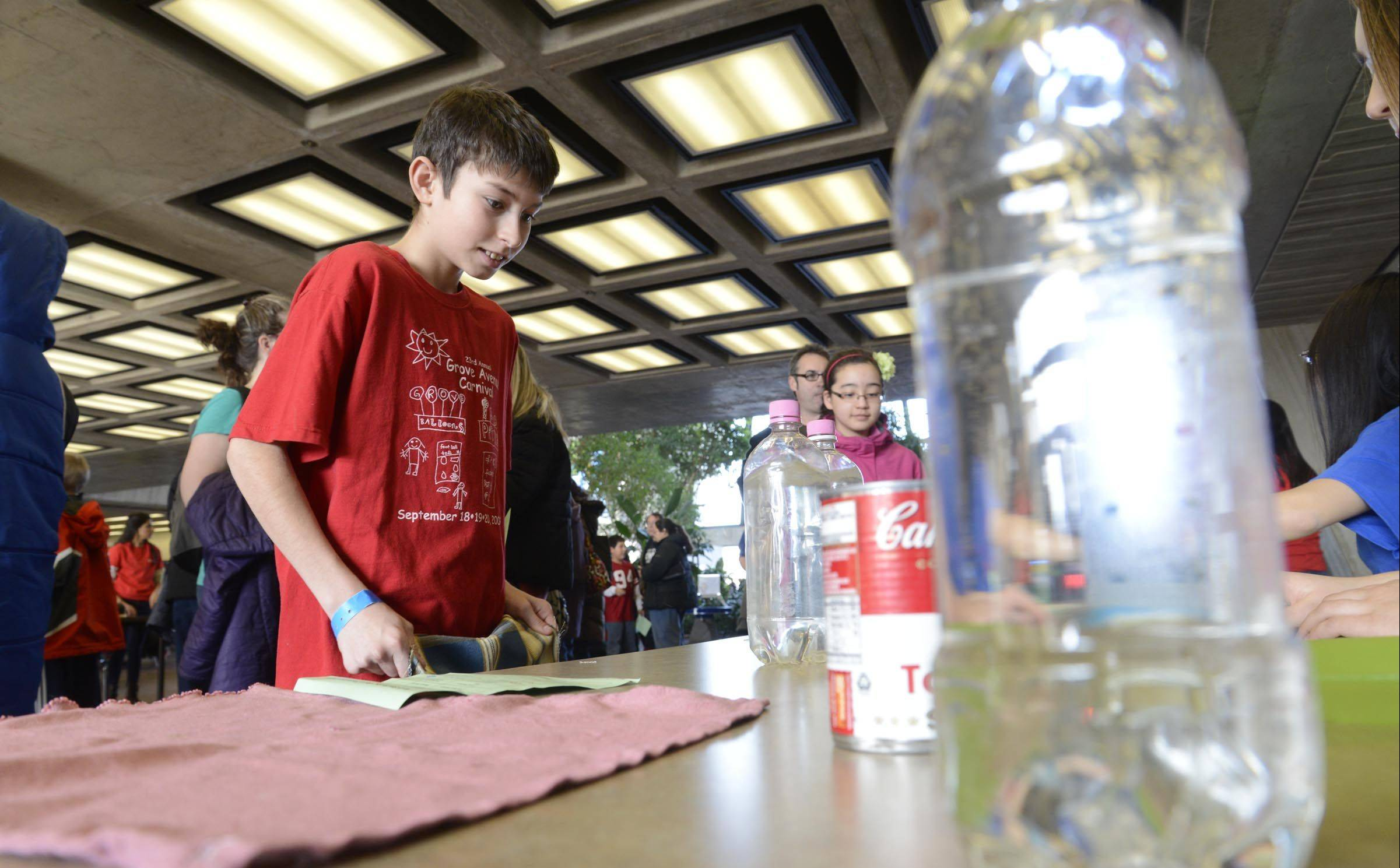 Above, Brendan Barnett, 11, of Hoffman Estates, tests theories of friction while pulling a cloth out from under objects Sunday at the Fermi Lab Family Open House in Batavia. Below, Richard Yang, 10, of Wheaton, spins a bucket full of Ping-Pong balls. He was doing an experiment to test centripetal force. About 2,000 children and families attended the annual event where kids get to try hands-on experiments and meet scientists.