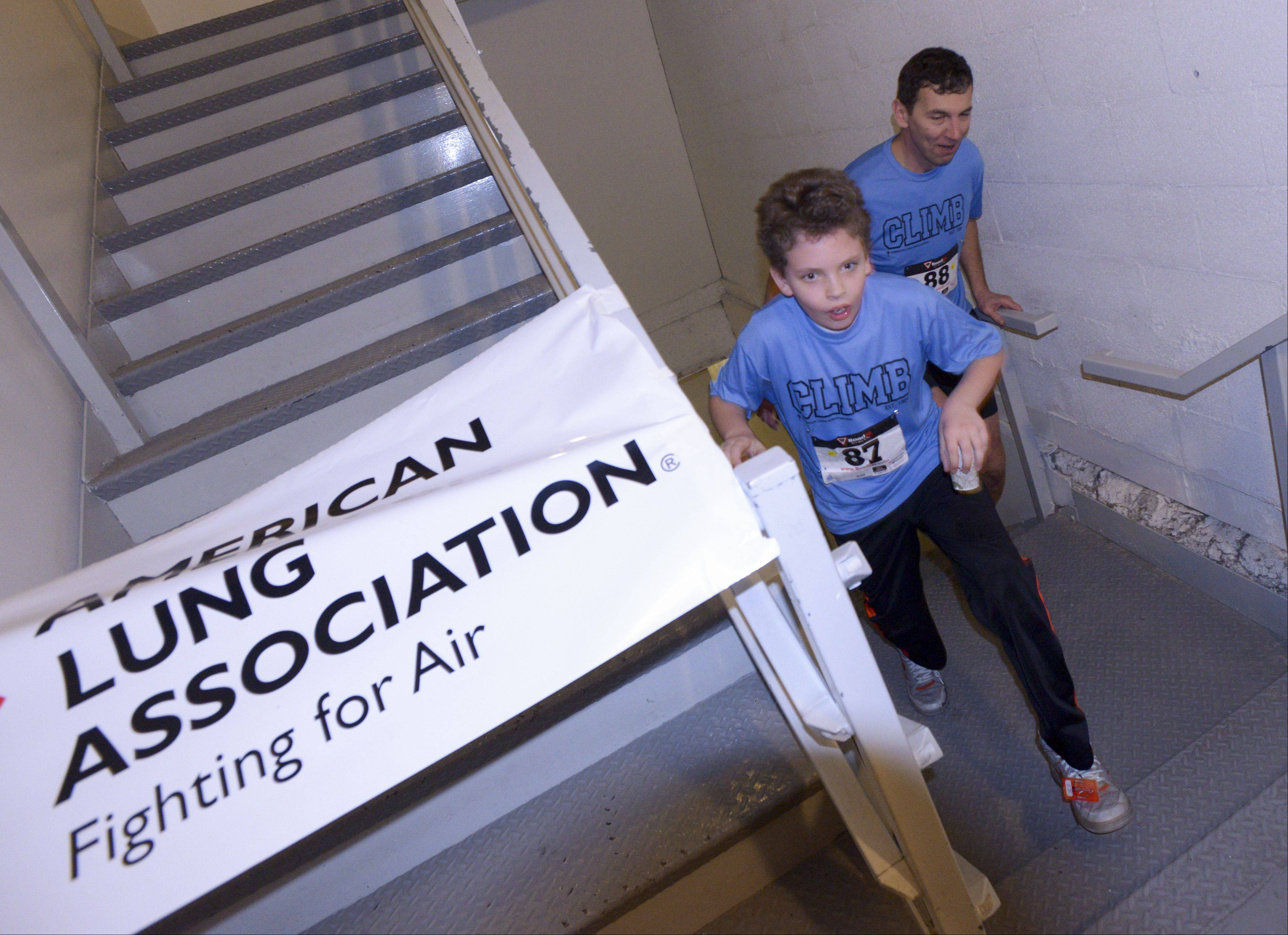 Frank Finnegan, 11, of Darien reaches the top a few steps ahead of his dad, Rob, during Sunday's Fight for Air Climb at the Oakbrook Terrace Tower to benefit the American Lung Association. The tower is the tallest building in the suburbs.