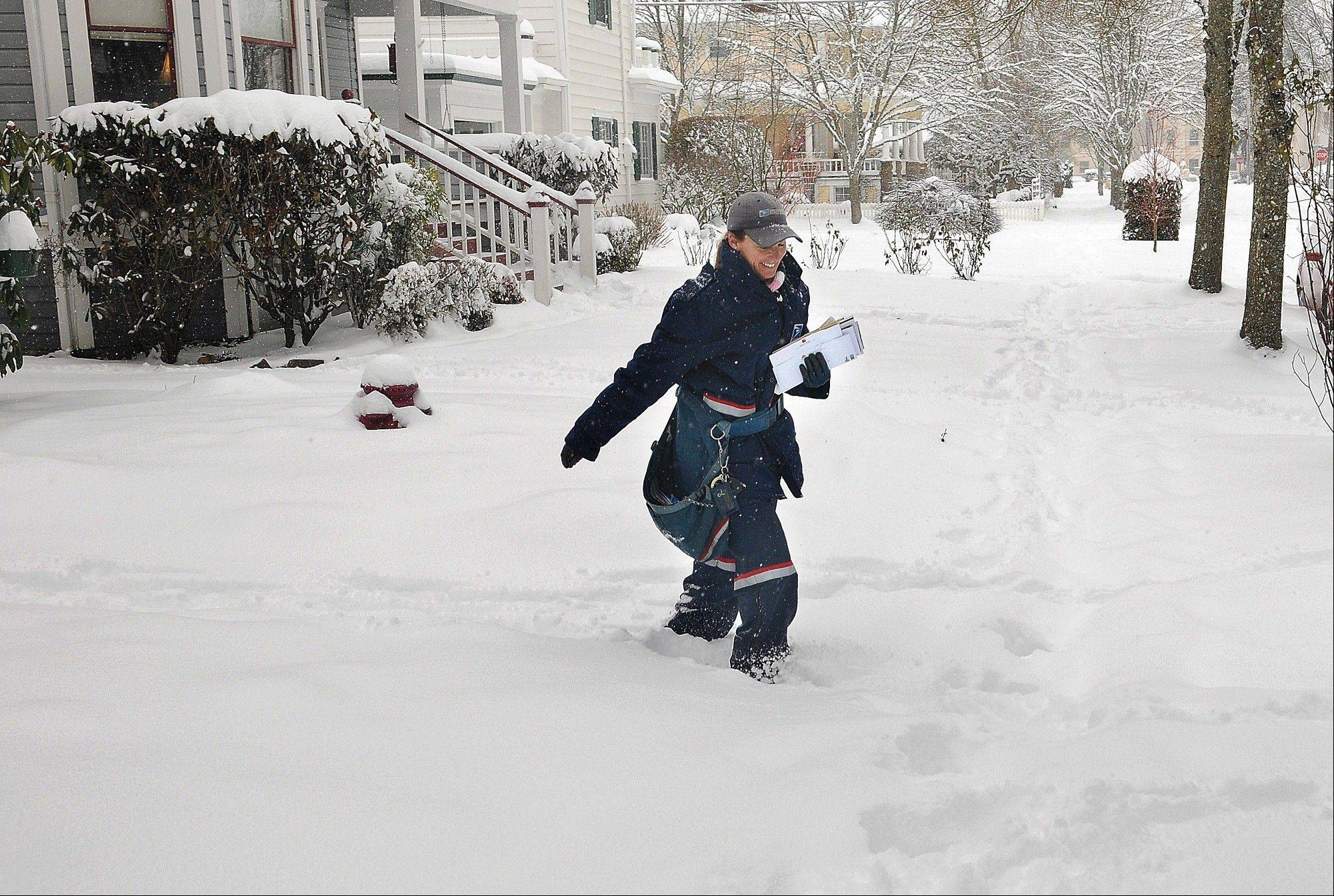 Mail carrier Tammie Harris trudges through the snow while delivering to homes in the Monteith District of Albany, Ore., Friday. More than a foot of snow has fallen in the Willamette Valley community during the last two days. The area, known for its rain, rarely sees more than a few inches of the white stuff a year.