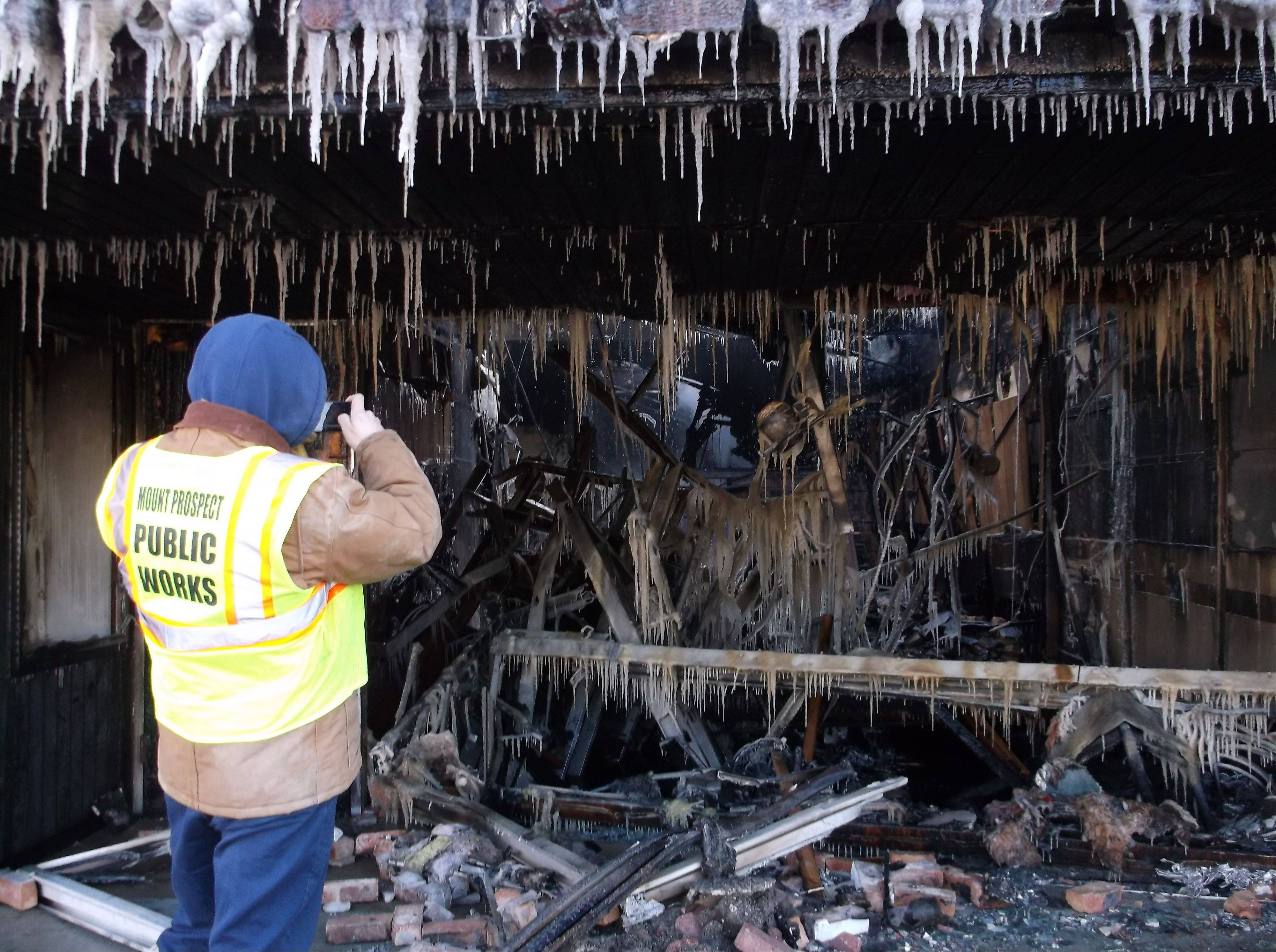 A Mount Prospect public works employee examines the gutted remains of a restaurant damaged by an early morning fire Sunday. No one was injured in the blaze, the cause of which is under investigation.