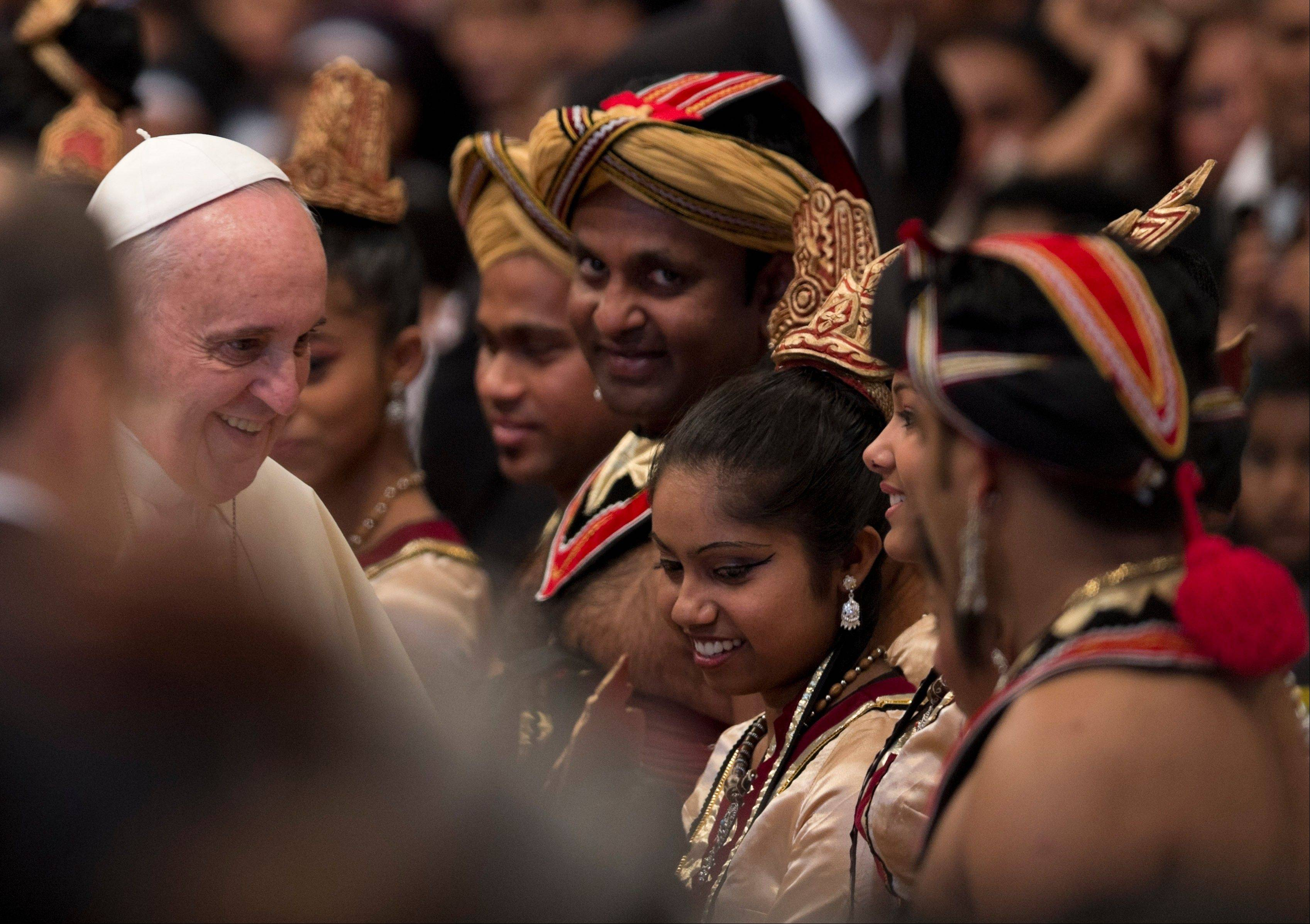 Pope Francis greets Sri Lankan dancers Saturday who performed during a mass for their community in St. Peter's Basilica at the Vatican.